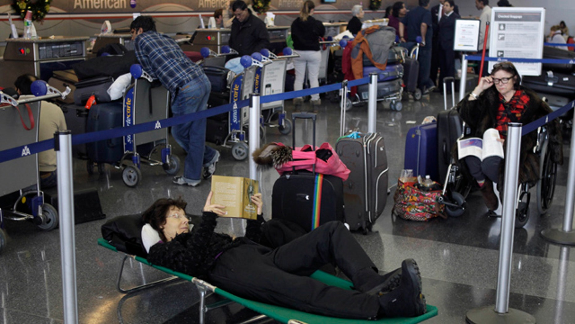 Dec. 27, 2010: Air passengers that stayed overnight in the airport pass the time while waiting for news of their canceled flights at John F. Kennedy International Airport in New York.