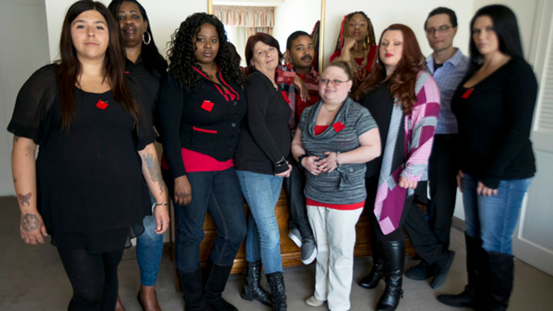 March 30, 2015: Makenzie Vasquez, from left, Pamala Hunt, Latonya Suggs, Ann Bowers, Nathan Hornes, Ashlee Schmidt, Natasha Hornes, Tasha Courtright, Michael Adorno and  Sarah Dieffenbacher, pose for a picture in Washington. Former and current college students calling themselves the Corinthian 100 say they are on a debt strike and refuse to pay back their student loans. (AP Photo/Manuel Balce Ceneta)