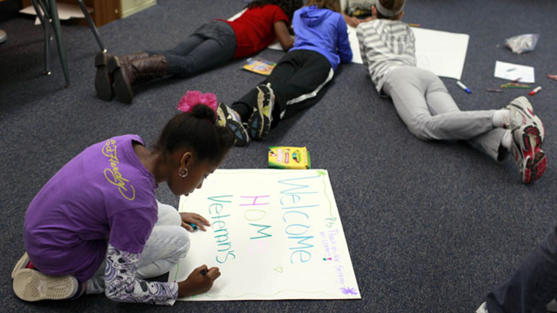 """January 25, 2012: Niliah Banks, foreground, works with other students in her fifth grade class at Ross Elementary create hand-made signs in Creve Coeur, Mo. The signs will be used when St. Louis hosts a """"Welcome Home the Heroes from Iraq Day"""" on Jan. 28."""