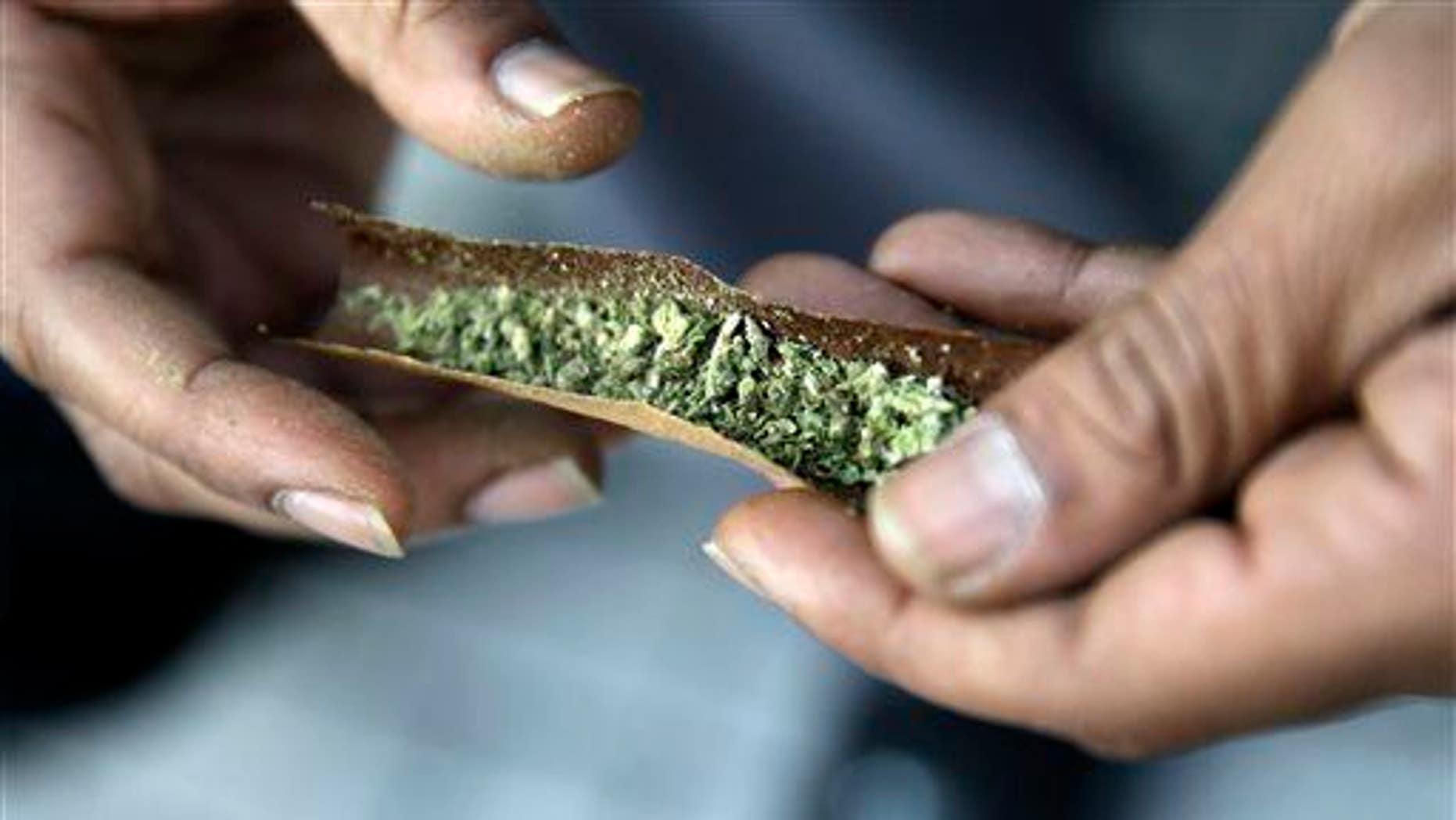A man rolls a marijuana cigarette on Saturday, March 21, 2015, in Trenton, N.J.