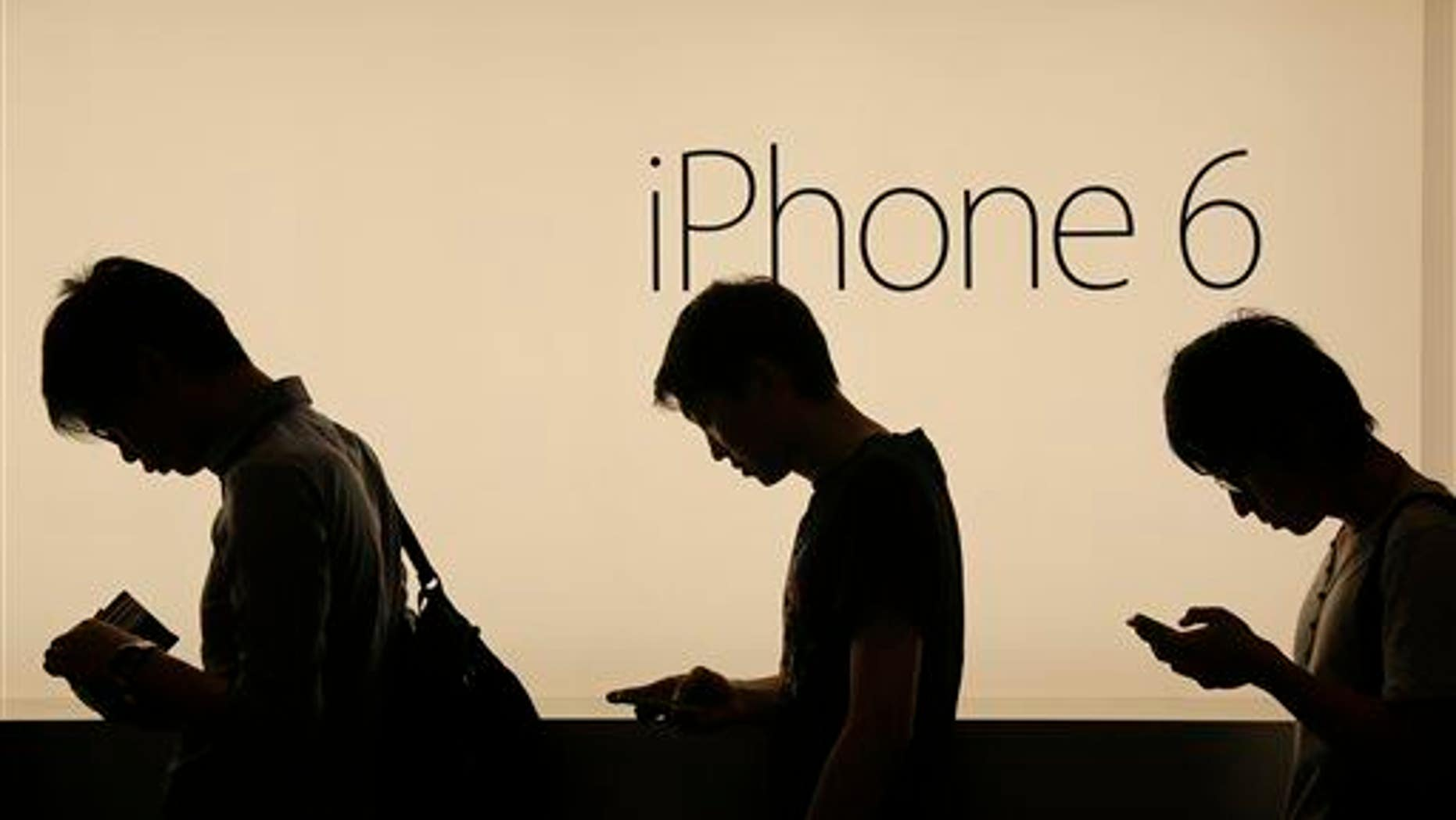In this photo taken on Friday, Sept. 19, 2014, people wait outside an Apple store in Hong Kong.