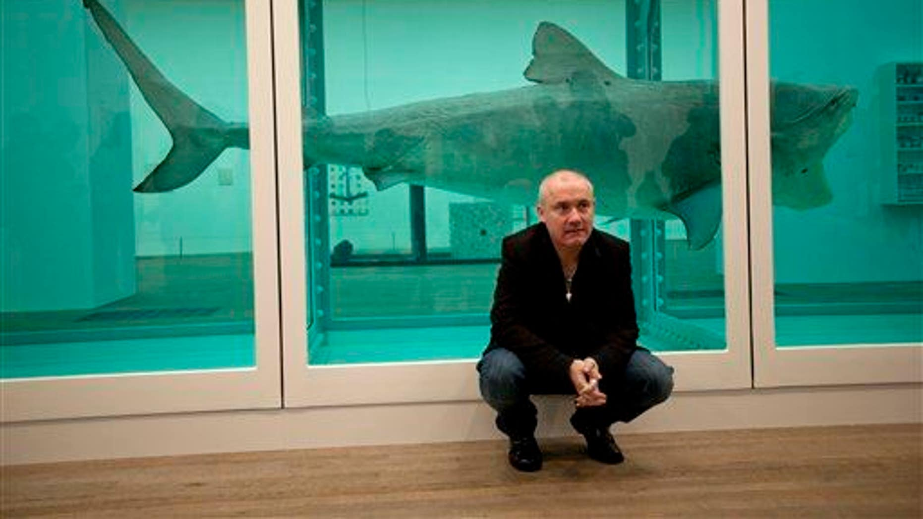 """Damien Hirst poses beside his piece """"The Physical Impossibility of Death in the Mind of Someone Living"""" in 2012 at the Tate. Death was actually not so impossible, as a new study finds the piece was leaking poisonous gas."""