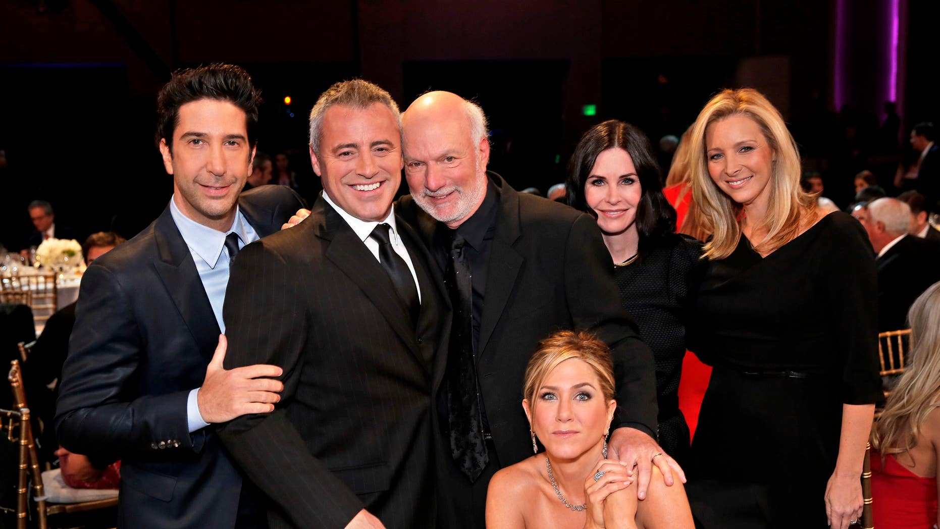 """In this image released by NBC, director James Burrows, standing center, poses with the cast of """"Friends,"""" from left,  David Schwimmer, Matt LeBlanc, Jennifer Aniston, seated, Courteney Cox and Lisa Kudrow."""