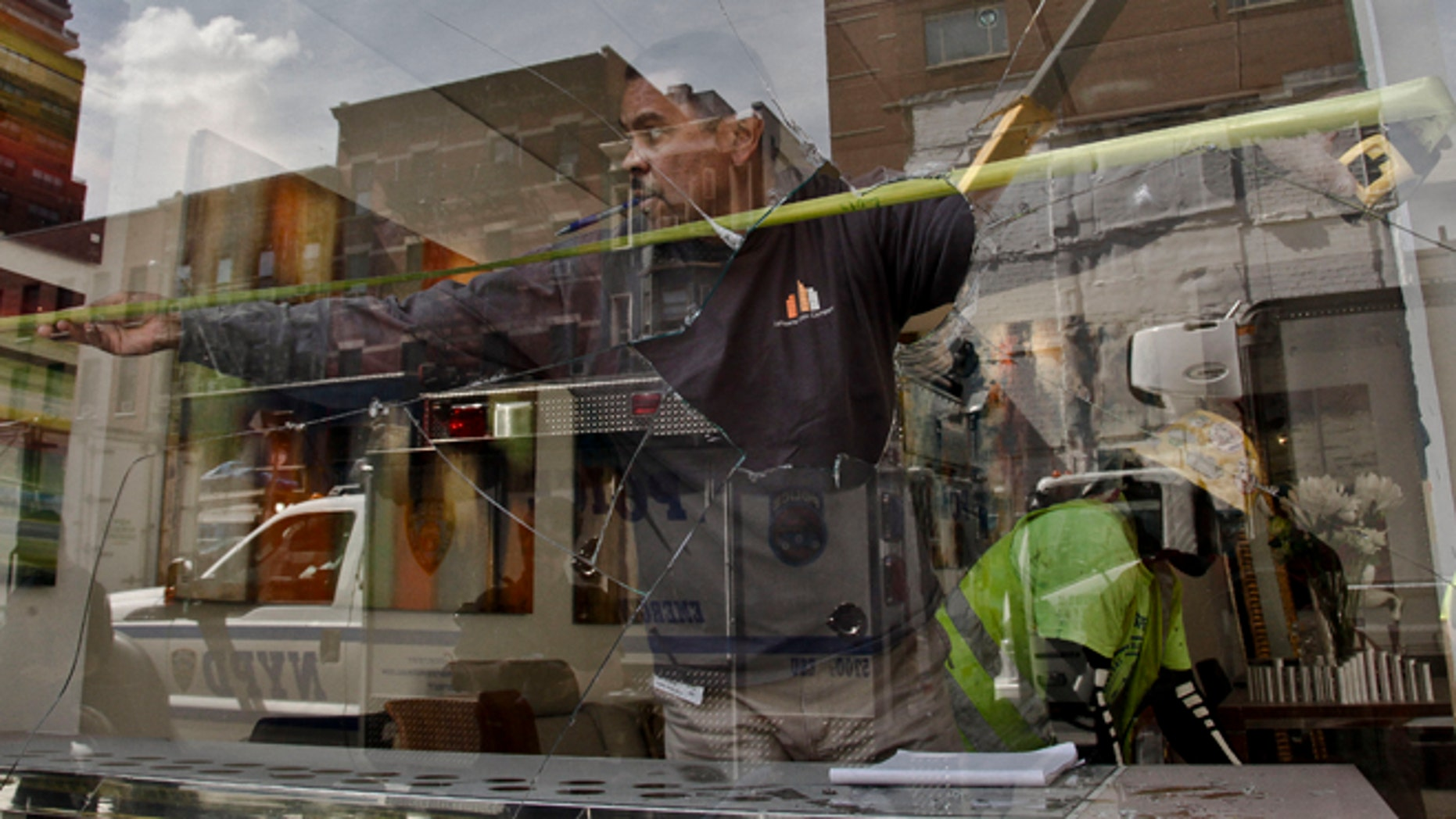 Aug. 21, 2012: A workers measure the area of a shattered window at the Kolb Art Gallery following damage from an intentional underground explosion on the Second Avenue subway project on East 72nd Street.