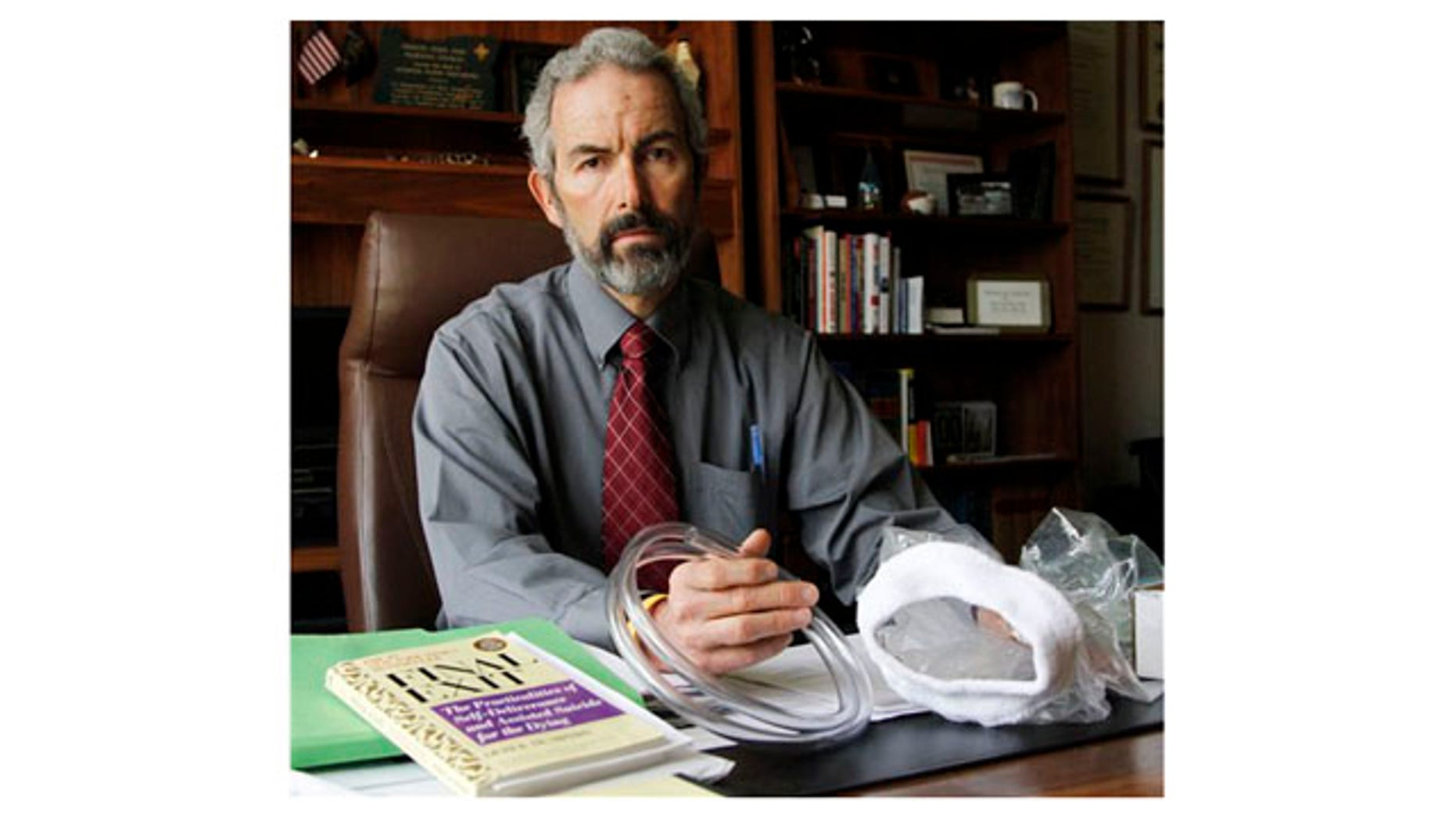 """May 12: Oregon State Sen. Floyd Prozanski shows a suicide kit consisting of the book """"Final Exit"""", plastic tubing and a plastic bag with collar that fits over a person's head at his Capitol office in Salem, Ore."""