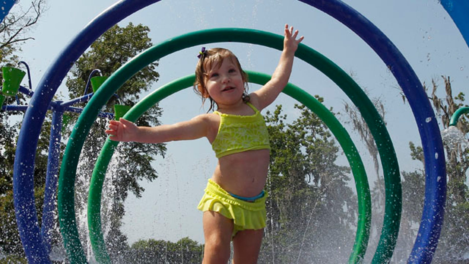 FILE: Alivia Parker, 21 months, runs through circles of spraying water on a 100 degree day in Montgomery, Ala.