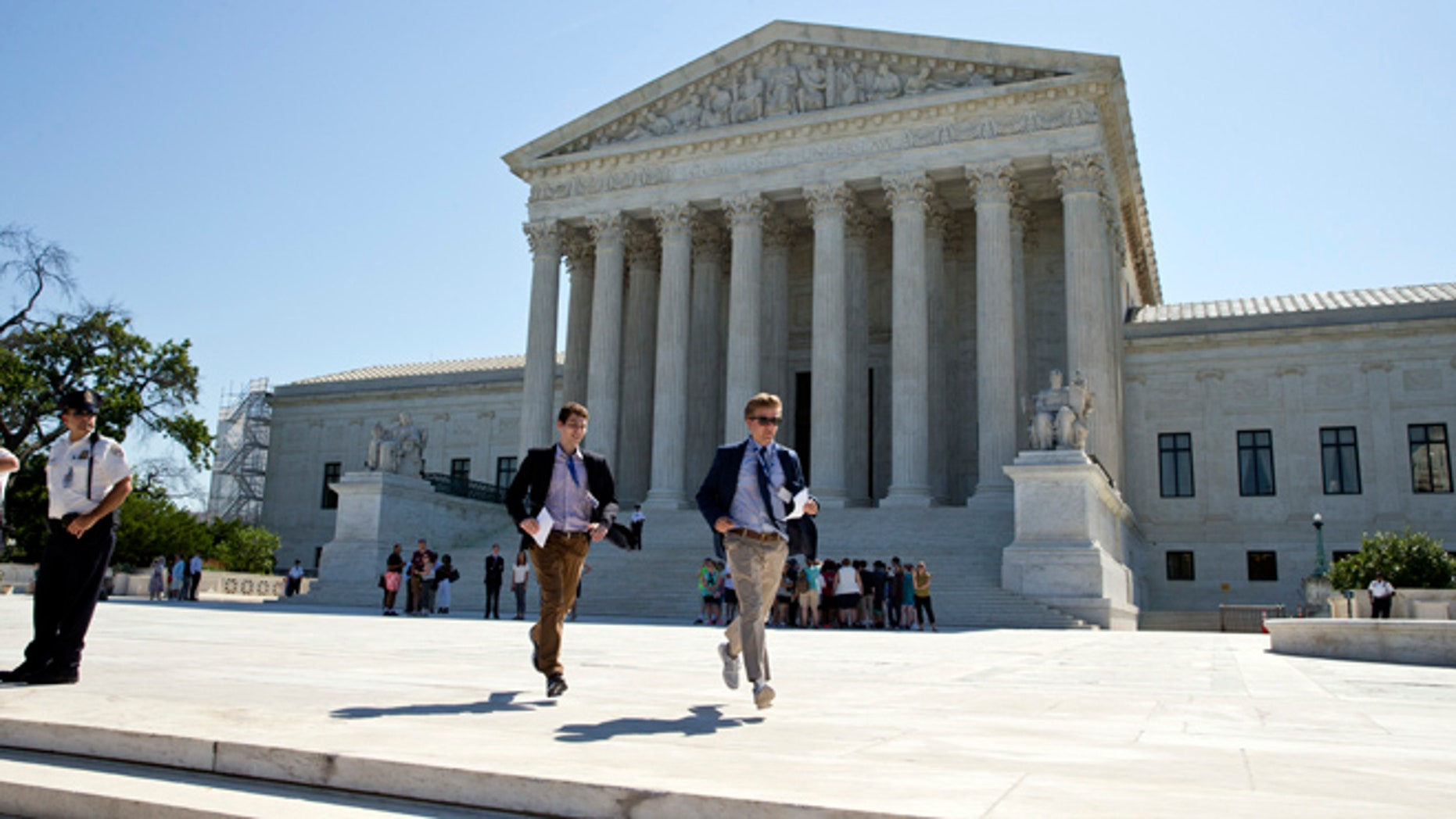 Gregory Briker, left, and John Bat, both with CBS News, run from the Supreme Court in Washington, Monday, June 20, 2016, with papers announcing court decisions. (AP Photo/Alex Brandon)