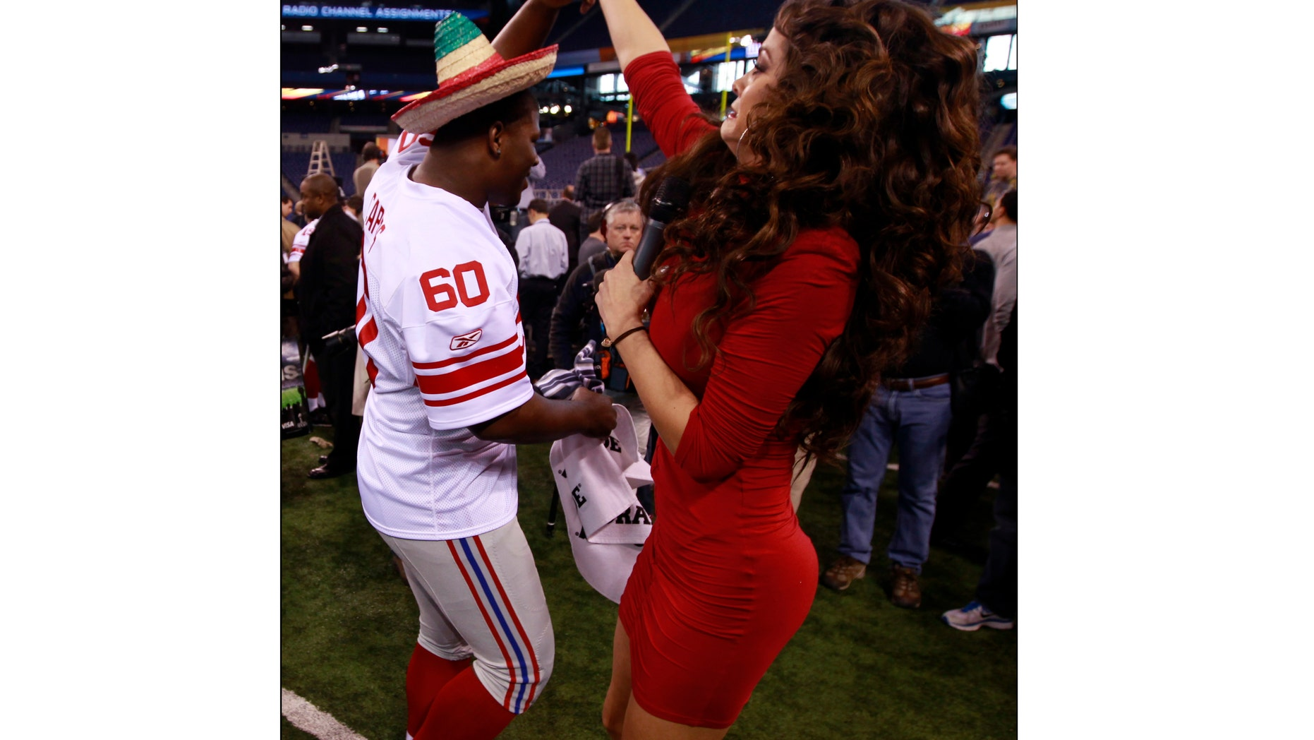 Marisol Gonzalez, Televisa reporter, dances with Selvish Capers of the Giants, Jan. 31, 2012, in Indianapolis.