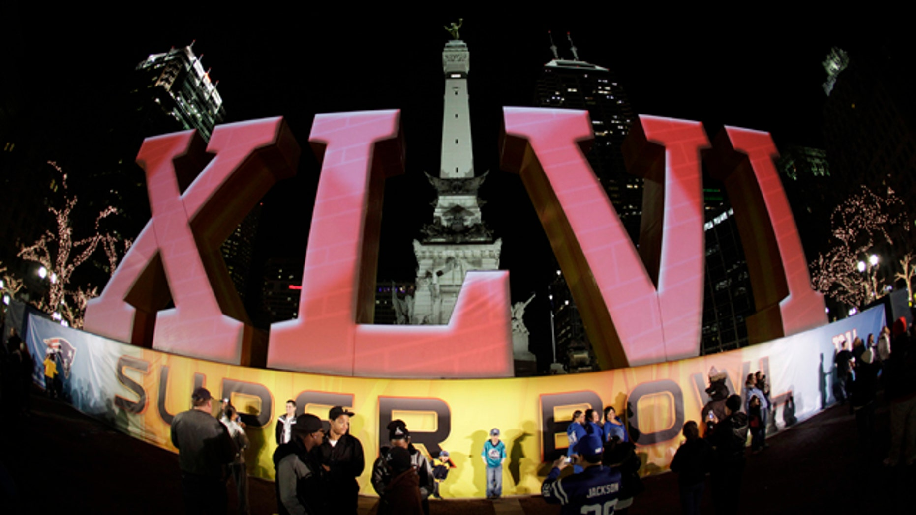 Feb. 1, 2012: In this photo taken with a fisheye lens, football fans pose for photos in front of the Super Bowl XLVI logo on Monument Circle in Indianapolis. The New England Patriots are scheduled to face the New York Giants in Super Bowl XLVI on Feb. 5.