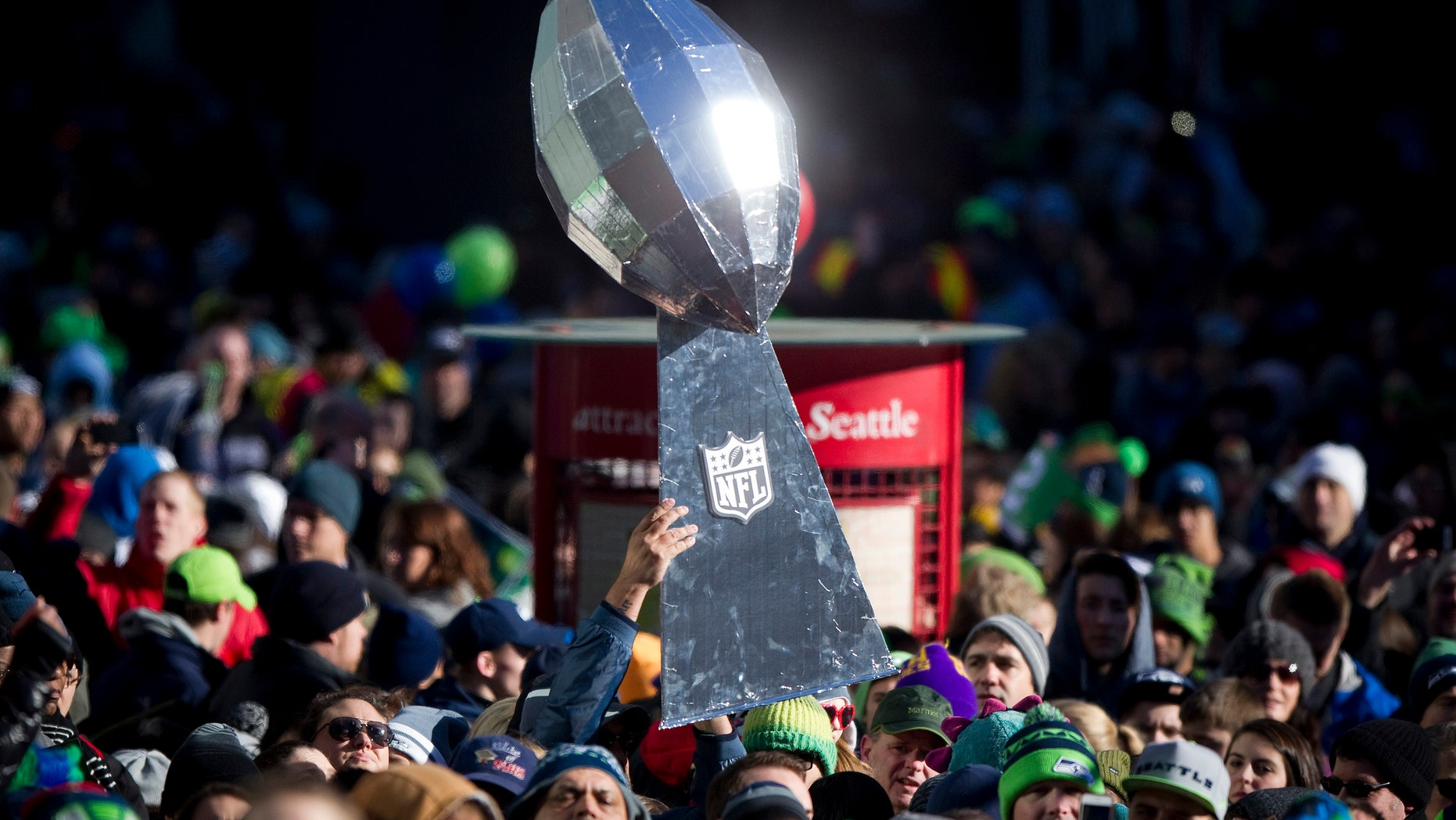 A Seattle Seahawks fan holds a giant Lombardi Trophy Super Bowl during the NFL team's Super Bowl victory parade in Seattle, Washington Feb. 5, 2014.