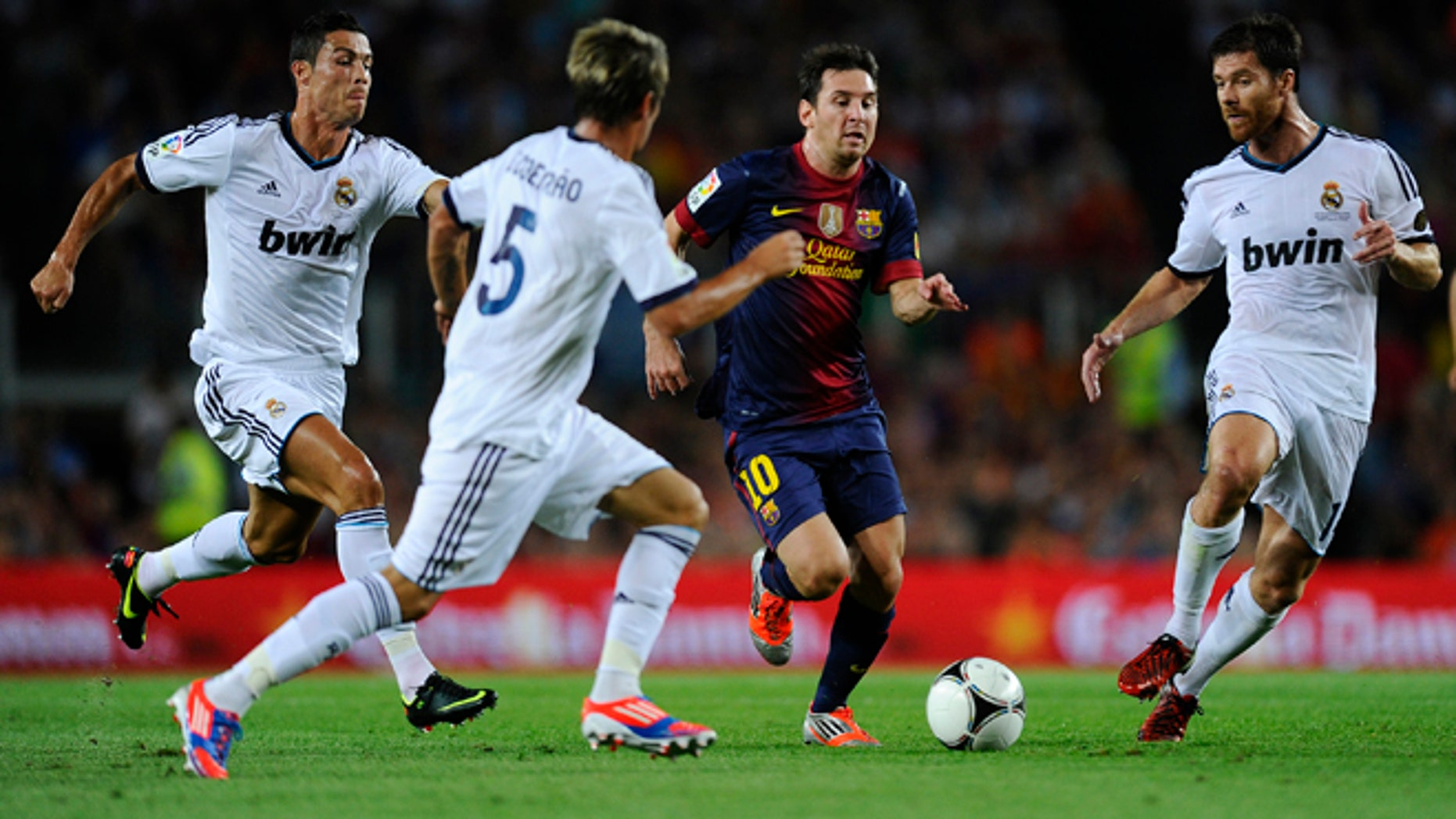 BARCELONA, SPAIN - AUGUST 23: Lionel Messi of FC Barcelona (2ndR) duels for the ball with Cristiano Ronaldo, Fabio Coentrao (2ndL) and Xabi Alonso of Real Madrid CF during the Super Cup first leg match between FC Barcelona and Real Madrid at Camp Nou on August 23, 2012 in Barcelona, Spain.  (Photo by David Ramos/Getty Images)