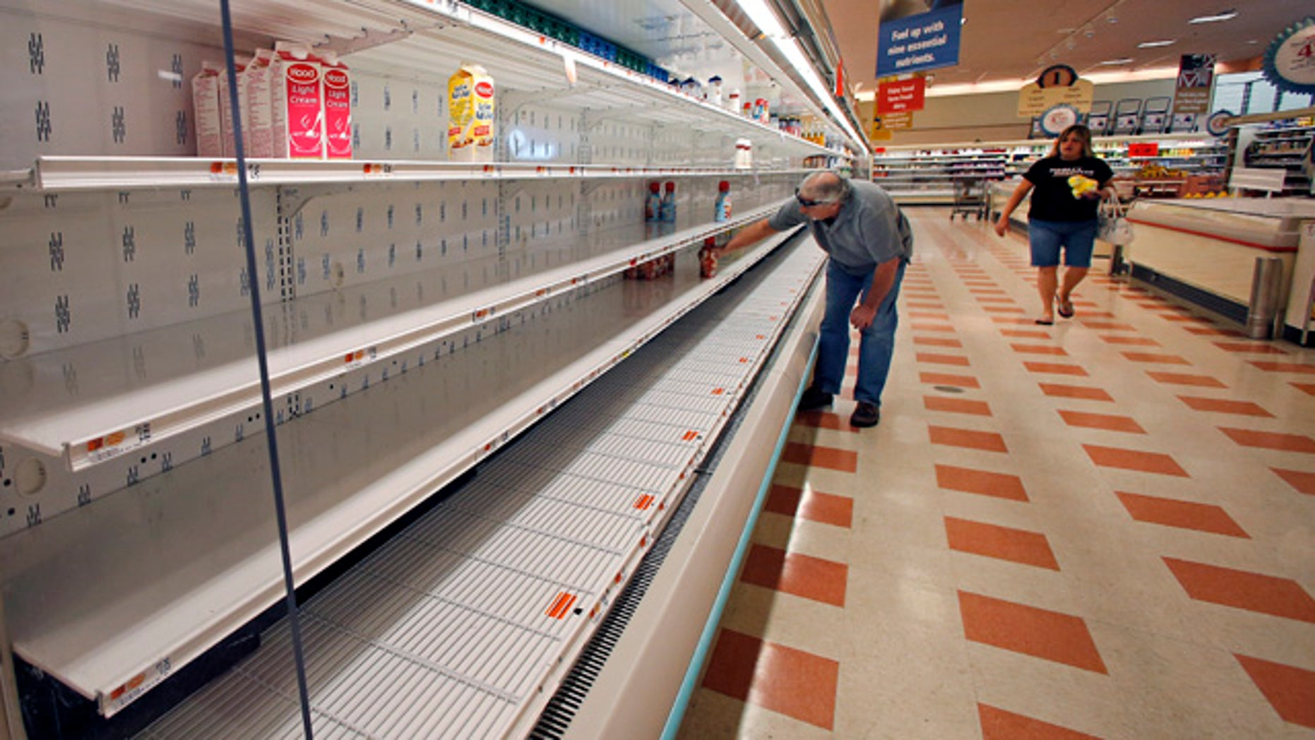 August 18, 2014: A shopper reaches into a mostly empty dairy shelf at Market Basket in Haverhill, Mass. (AP Photo/Elise Amendola)