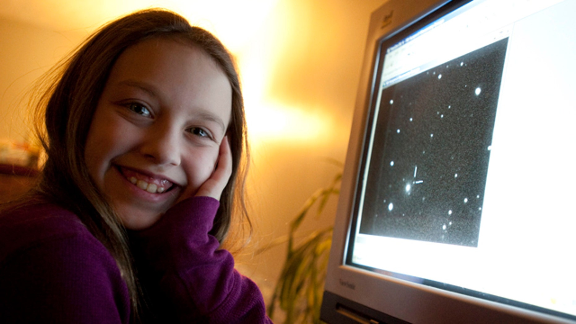 Ten-year-old Kathryn Gray sits next to a computer at the family's home in Birdton, New Brunswick, Canada, a suburb of Fredericton, on Monday, Jan. 3, 2011. On the computer monitor is an image in which she discovered a supernova. The Royal Astronomical Society of Canada says she made the discovery on the weekend under the watch of two other astronomers.