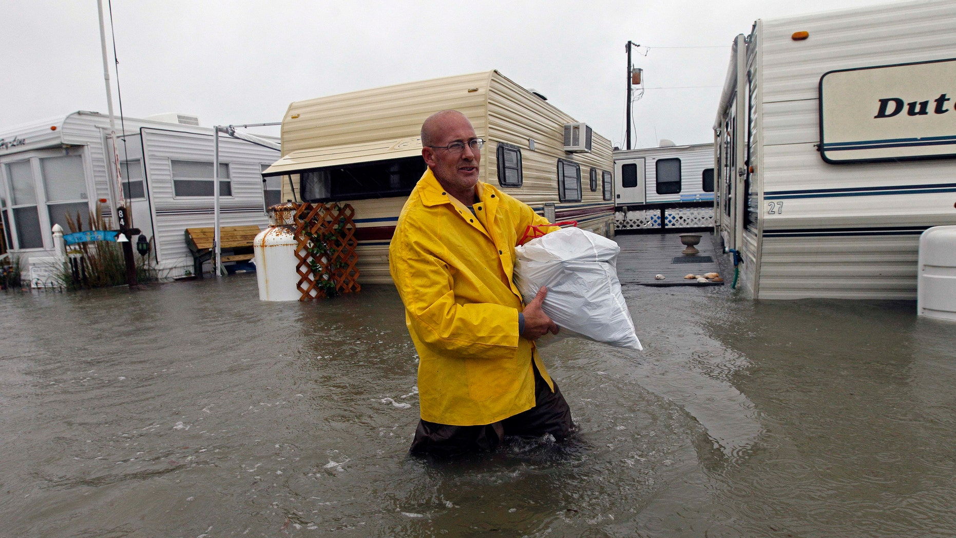 Oct. 29, 2012: Terry Robinson wades through water after retrieving some of his belongings from his flooded trailer at RV Park in Kitty Hawk, N.C., Monday.