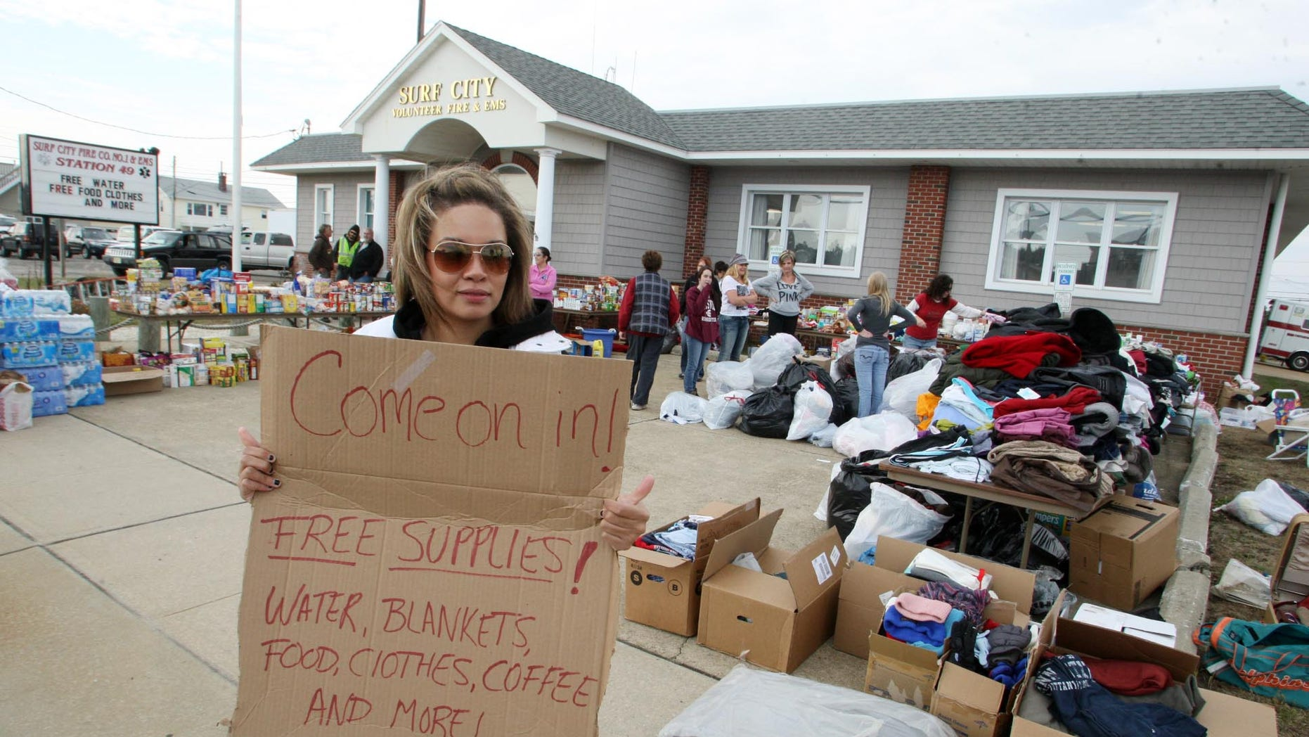 Nov. 10, 2012: Victoria Tribue, 21, volunteer member from Quakertown Pa., holds a sign advertising free supplies at the Surf City Volunteer Fire & EMS Station on Long Beach Island, N.J., after Superstorm Sandy.