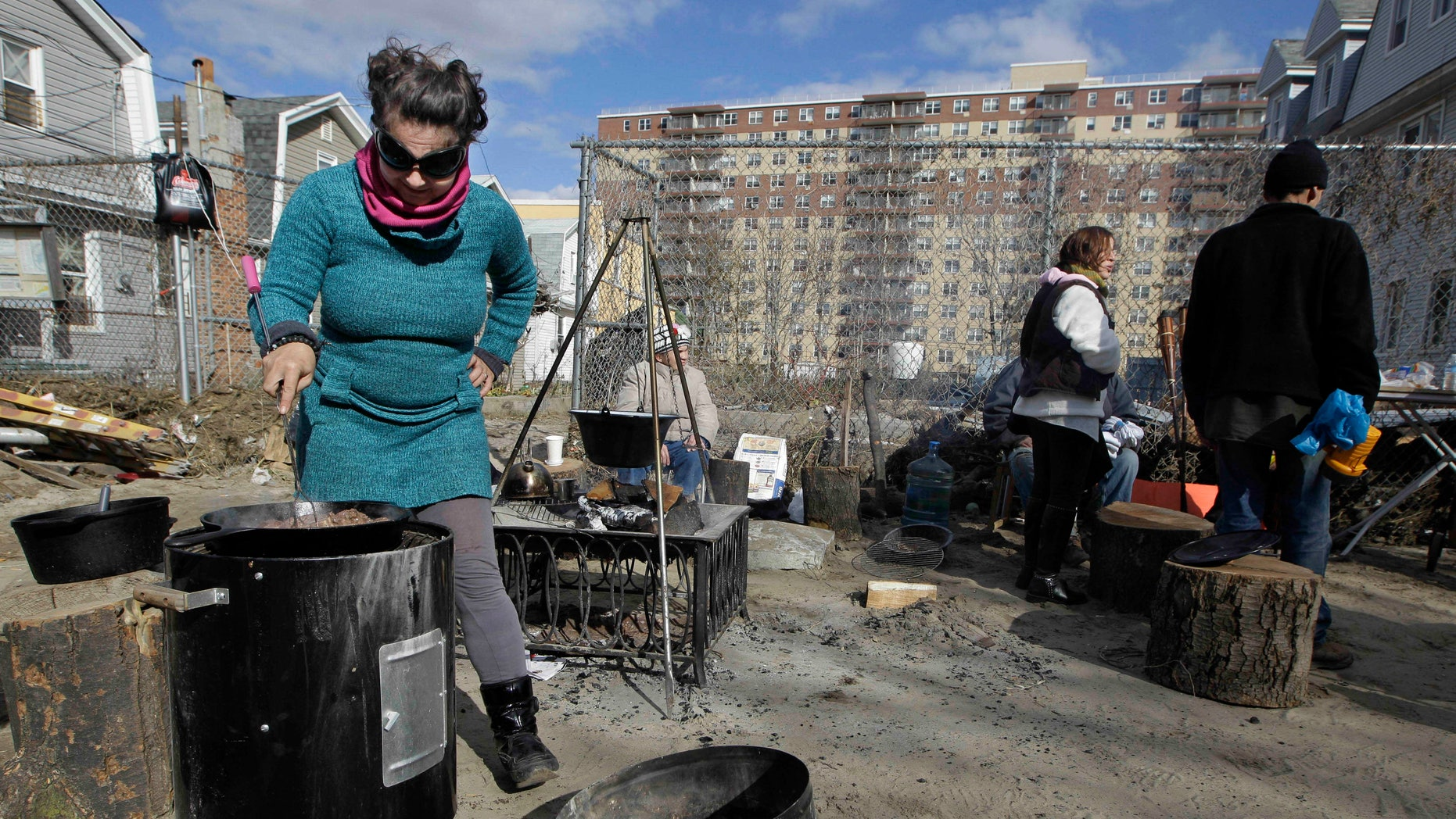 Nov. 3, 2012: Kiva Kahl prepares beef stew for friends and neighbors in front of her residence in the Rockaways section of New York. More New Yorkers awoke Saturday to power being restored for the first time since Superstorm Sandy pummeled the region, but patience wore thin among those in the region who have been without power for most of the week.
