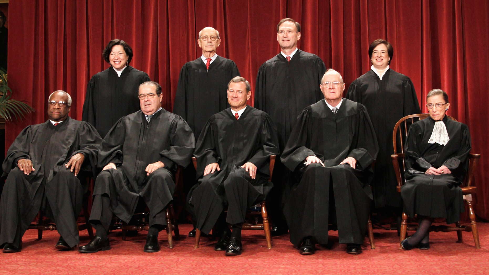 The justices of the U.S. Supreme Court at the Supreme Court in Washington. Seated from left are Associate Justices Clarence Thomas, and Antonin Scalia, Chief Justice John Roberts, Associate Justices Anthony M. Kennedy and Ruth Bader Ginsburg. Standing, from left are Associate Justices Sonia Sotomayor, Stephen Breyer, Samuel Alito Jr., and Elena Kagan.