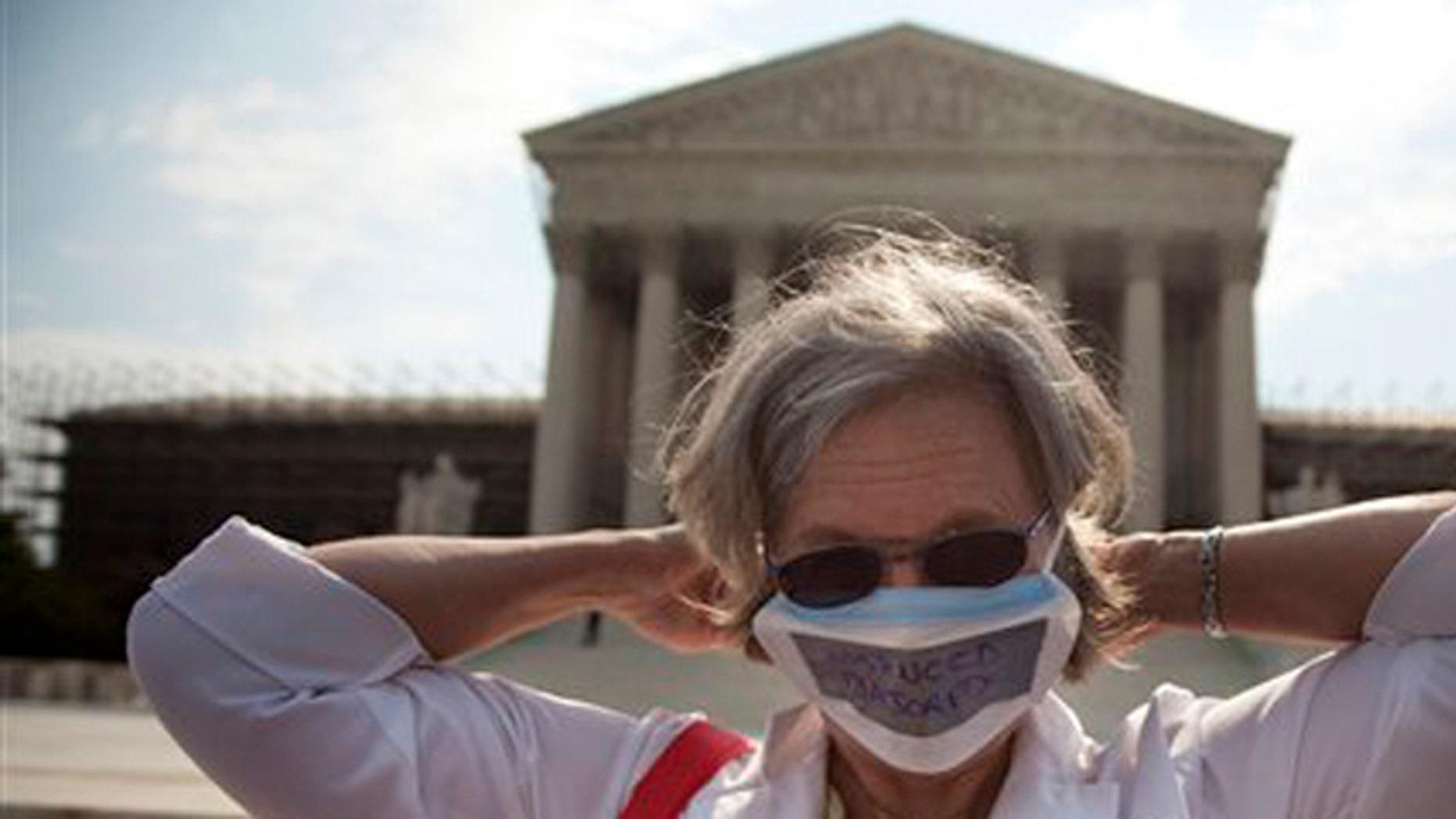 June 25, 2012: Carol Paris of Leonardtown, Md. demonstrates outside the Supreme Court in Washington.