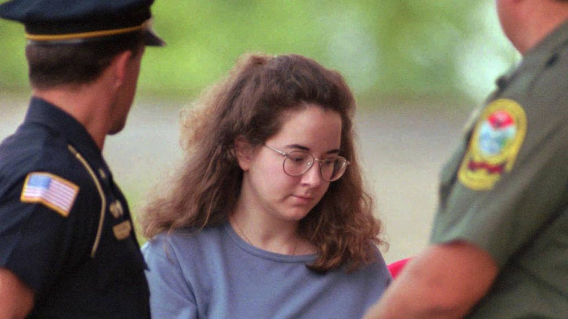 FILE - In this July 27, 1995 file photo, Susan Smith is escorted into the Union County Courthouse in Union, S.C. Smith sentenced to life in prison for killing her two young sons never planned to kill them and instead intended to end her own life, according to a letter she wrote to The State, a Columbia, S.C., newspaper, reported Wednesday, July 22, 2015.  (AP Photo/Lou Krasky, File)