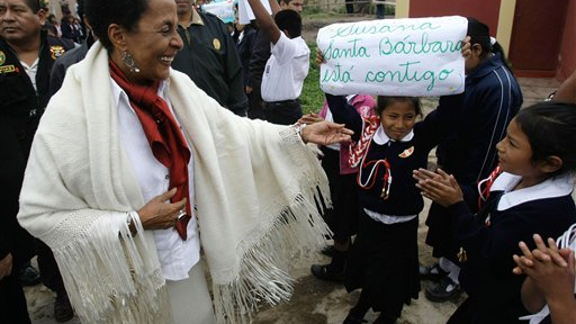 In this photo taken Aug. 29, 2011, Peru's Culture Minister Susana Baca greets students during a visit to a school in San Luis de Canete, Peru. Baca, 67, is living testimony to Afro-Peruvians' enduring struggle and she is determined to end the discrimination that made second-class citizens not just of blacks but also of Peru's indigenous. Baca became the Andean nation's first black Cabinet minister in July 2011.  (AP Photo/Karel Navarro)