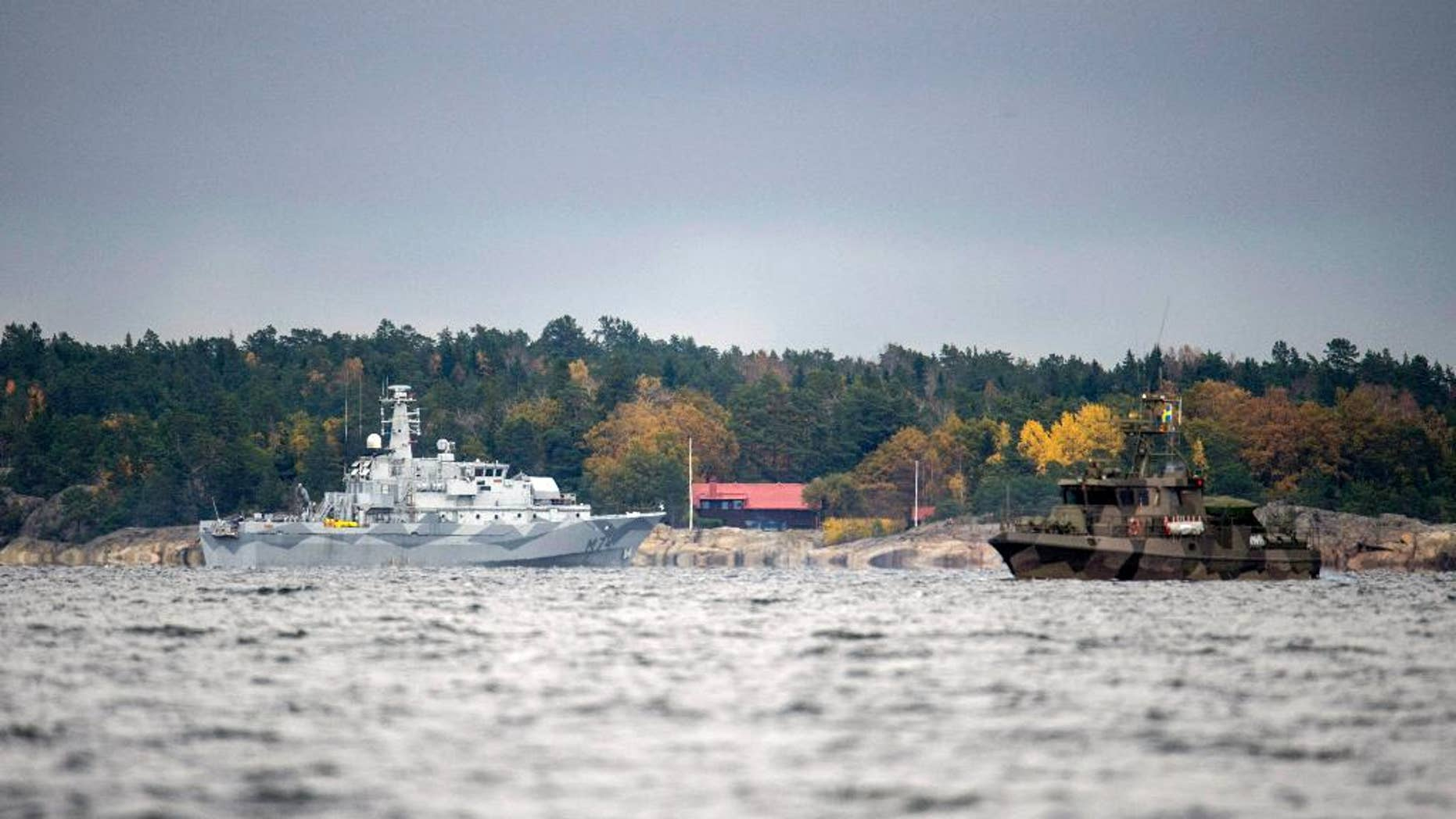 The Swedish minesweeper HMS Kullen, left, and a guard boat in Namdo Bay, Sweden,Tuesday, Oct. 21, 2014 on their fifth day of searching for a suspected foreign vessel in the Stockholm archipelago. The navy has demanded a 1000-meter (yard) no-go radius around naval vessels taking part in the current operation. (AP Photo/TT News Agency, Fredrik Sandberg)   SWEDEN OUT