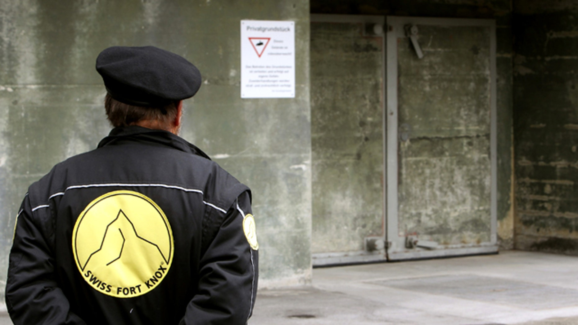 "A security guard stands in front of a gate of the Swiss Fort Knox bunker in the mountains near the Swiss Alpine resort of Saanen May 18, 2010. In the secret bunker, European researchers deposited a ""digital genome"" that will provide the blueprint for future generations to read data stored using defunct technology."