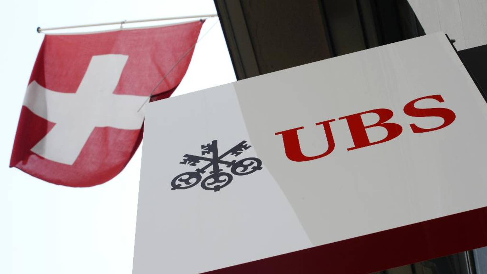 "FILE - The April 24, 2014 file photo shows the logo of Swiss bank UBS and the Swiss flag in Zurich, Switzerland.  UBS has reported a 71 percent increase in third quarter profit, Tuesday Nov. 3, 2015, as the banking giant took a big tax benefit, while predicting ""substantial"" future costs from new Swiss regulations aimed at bucking up the country's two biggest financial institutions. (Steffen Schmidt/Keystone via AP,File)"
