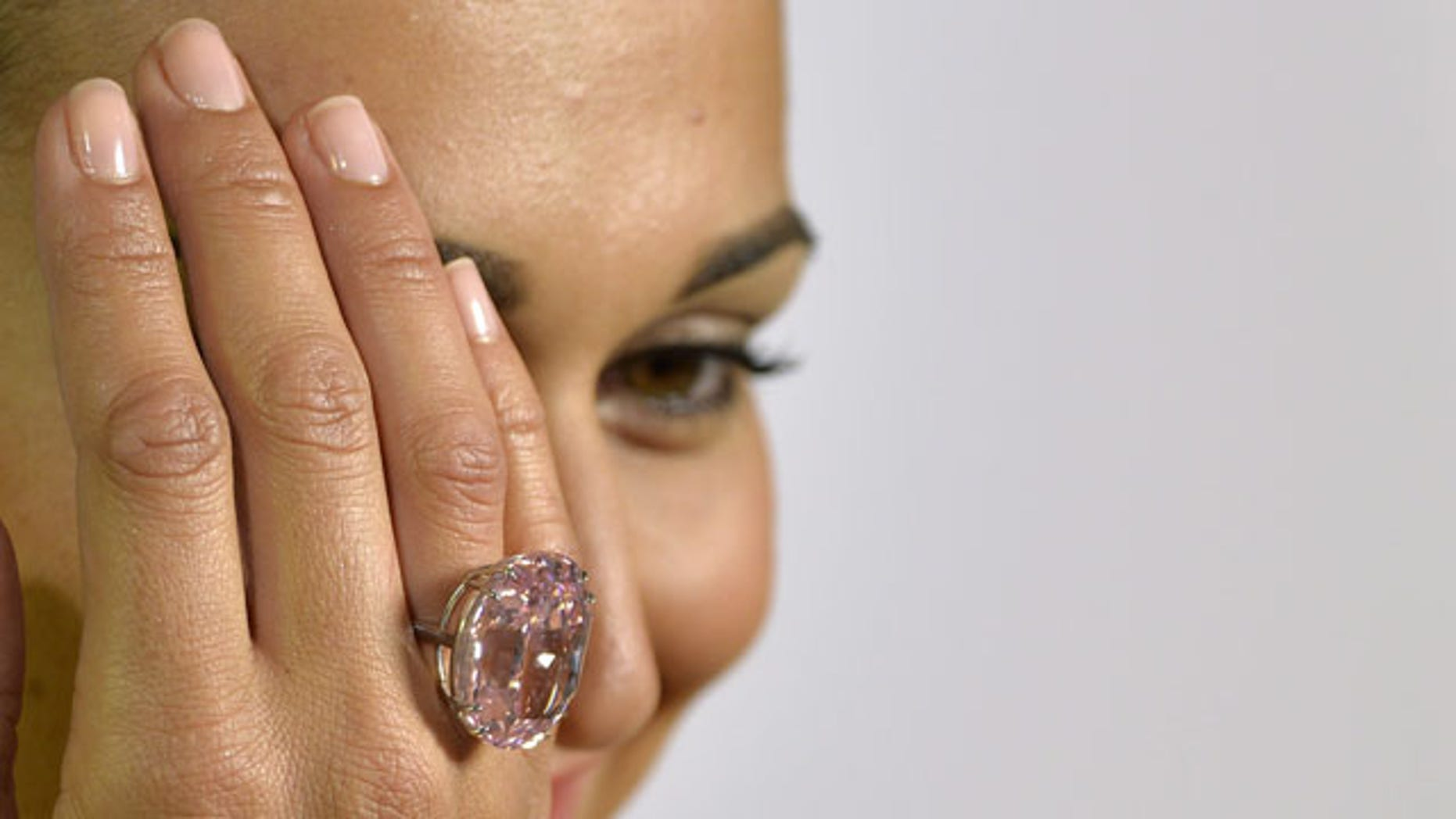 """FILE - A Wednesday, Sept. 25, 2013 photo from files showing an unidentified Sotheby's employee displaying """"The Pink Star"""" diamond weighing 59.6 carat, during a preview at Sotheby's, in Geneva, Switzerland. (AP Photo)"""