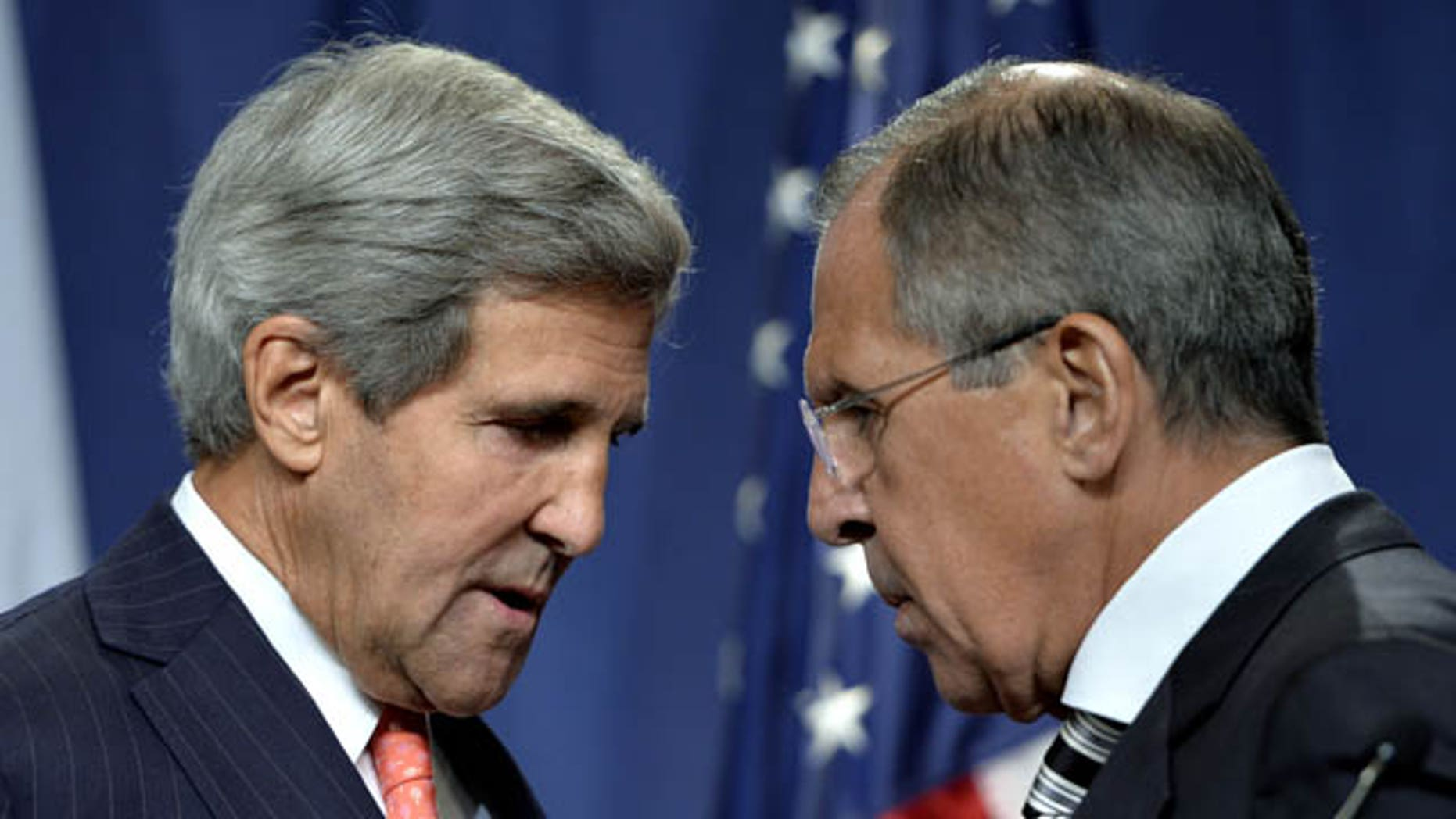 September 14, 2013: U.S. Secretary of State John Kerry, left, speaks with Russian Foreign Minister Sergei Lavrov, right, during a news conference in Geneva, Switzerland. (AP Photo/Keystone,Martial Trezzini)