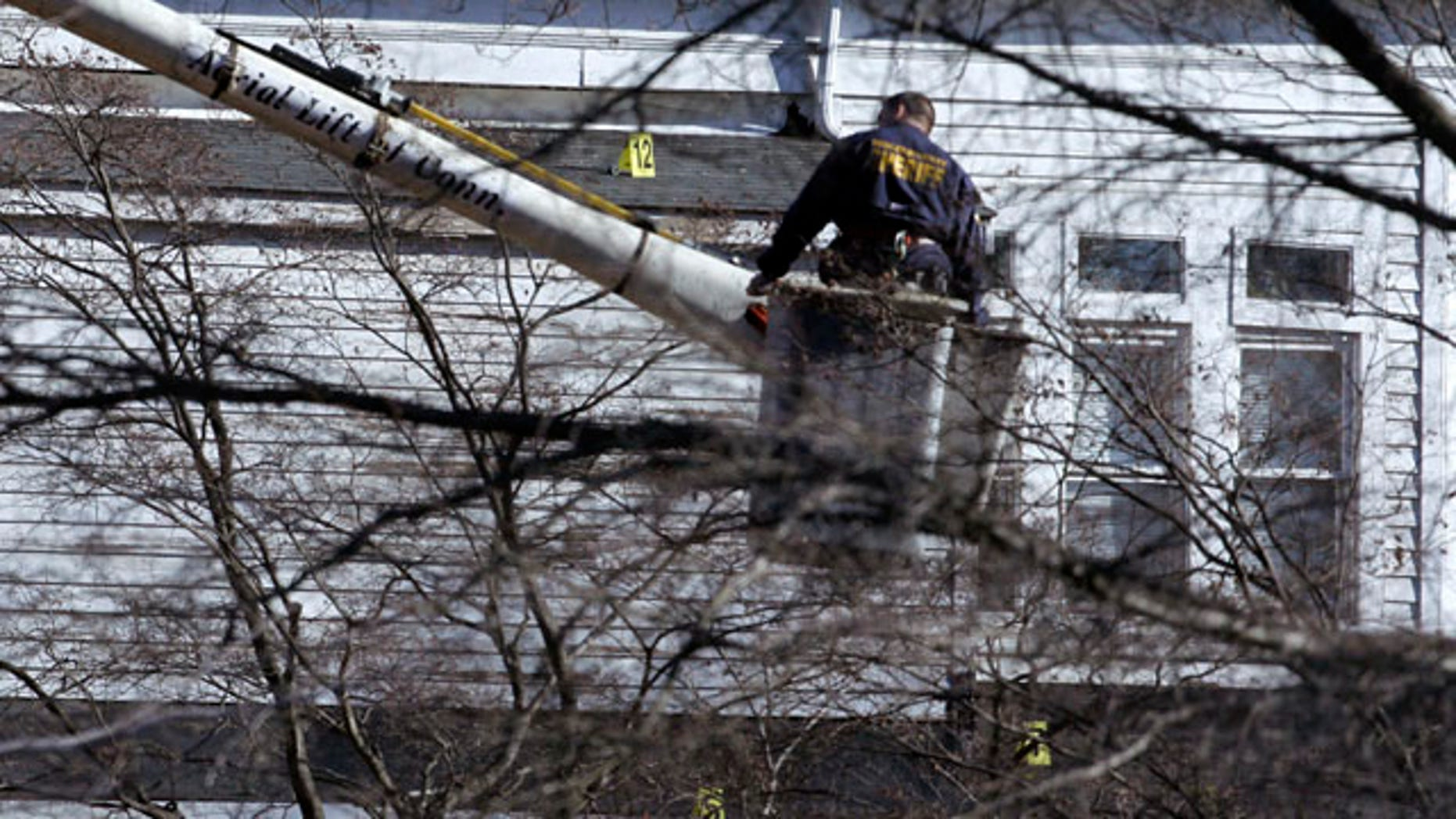 Jan. 11: A Bergen County Sheriff's investigator stands on a lift as markers sit on the roof of Congregation Beth El as authorities investigate an early morning fire.