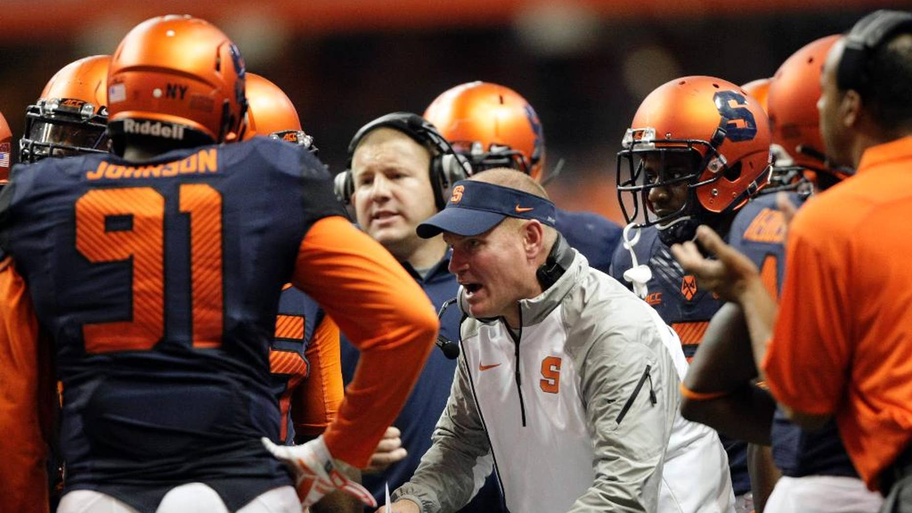 FILE - In this Oct. 3, 2014, file photo, Syracuse's head coach Scott Shafer talks to his players during a timeout in the third quarter of an NCAA college football game against Louisville in Syracuse, N.Y. Shafer has shuffled his staff as the Orange prepare to host top-ranked Florida State. (AP Photo/Nick Lisi, File)