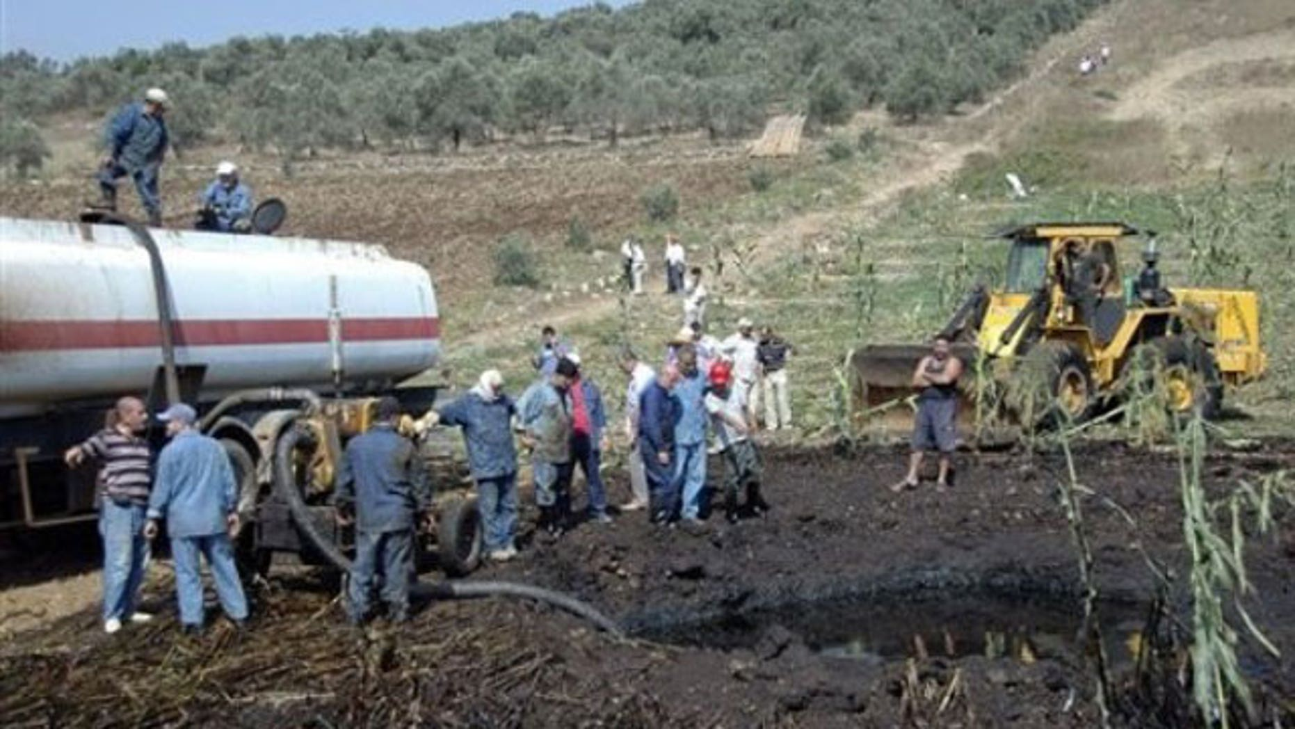 July 29, 2011: In this photo released by the Syrian official news agency SANA, workers pump oil from the site of a bomb blast that struck a major oil pipeline in the western town of Talkalakh, Syria.