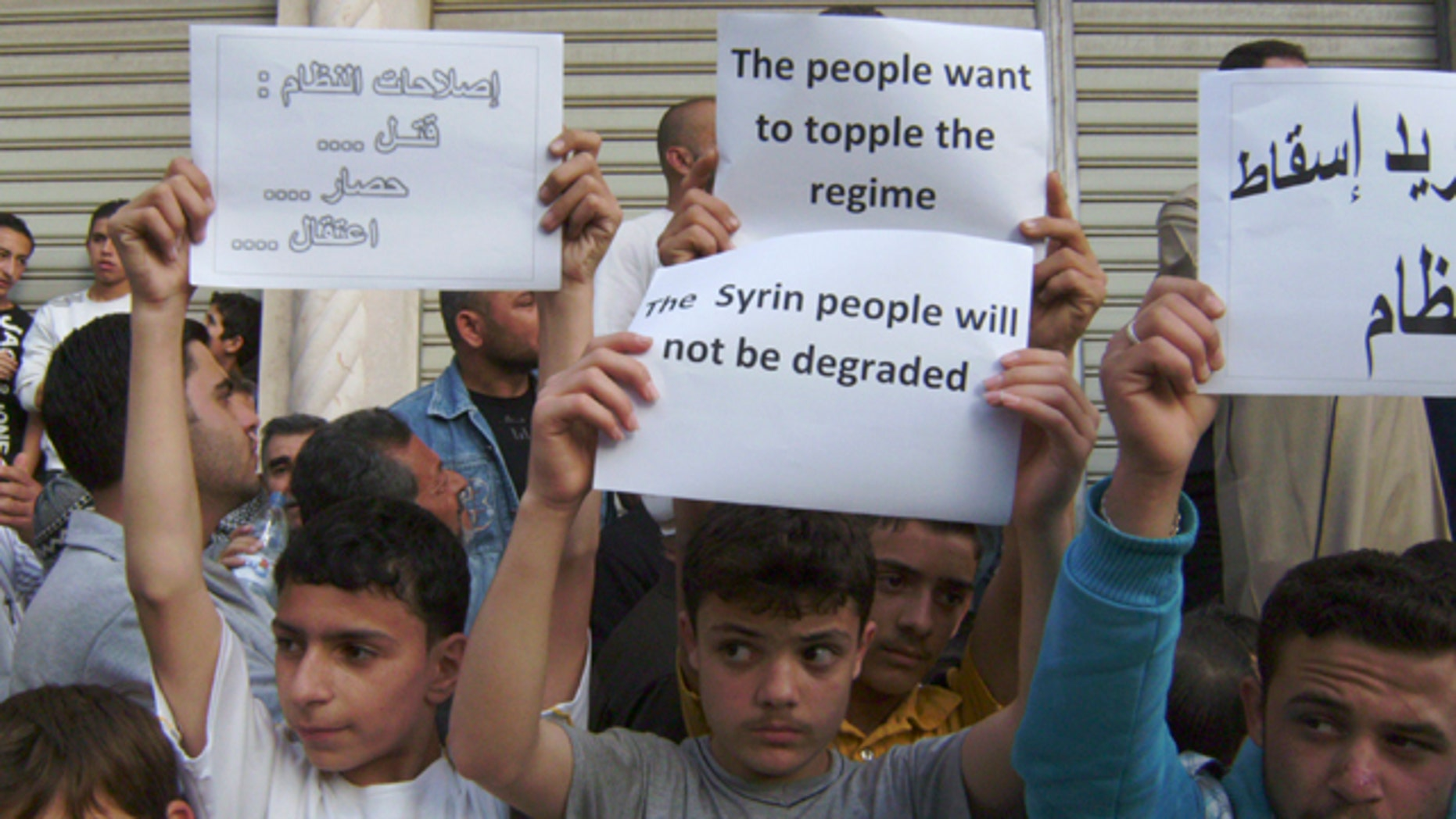 May 5, 2011: In this citizen journalism image made on a mobile phone and acquired by the AP, Syrians carry banners during a protest against the regime of President Assad, in the coastal town of Banias, Syria.