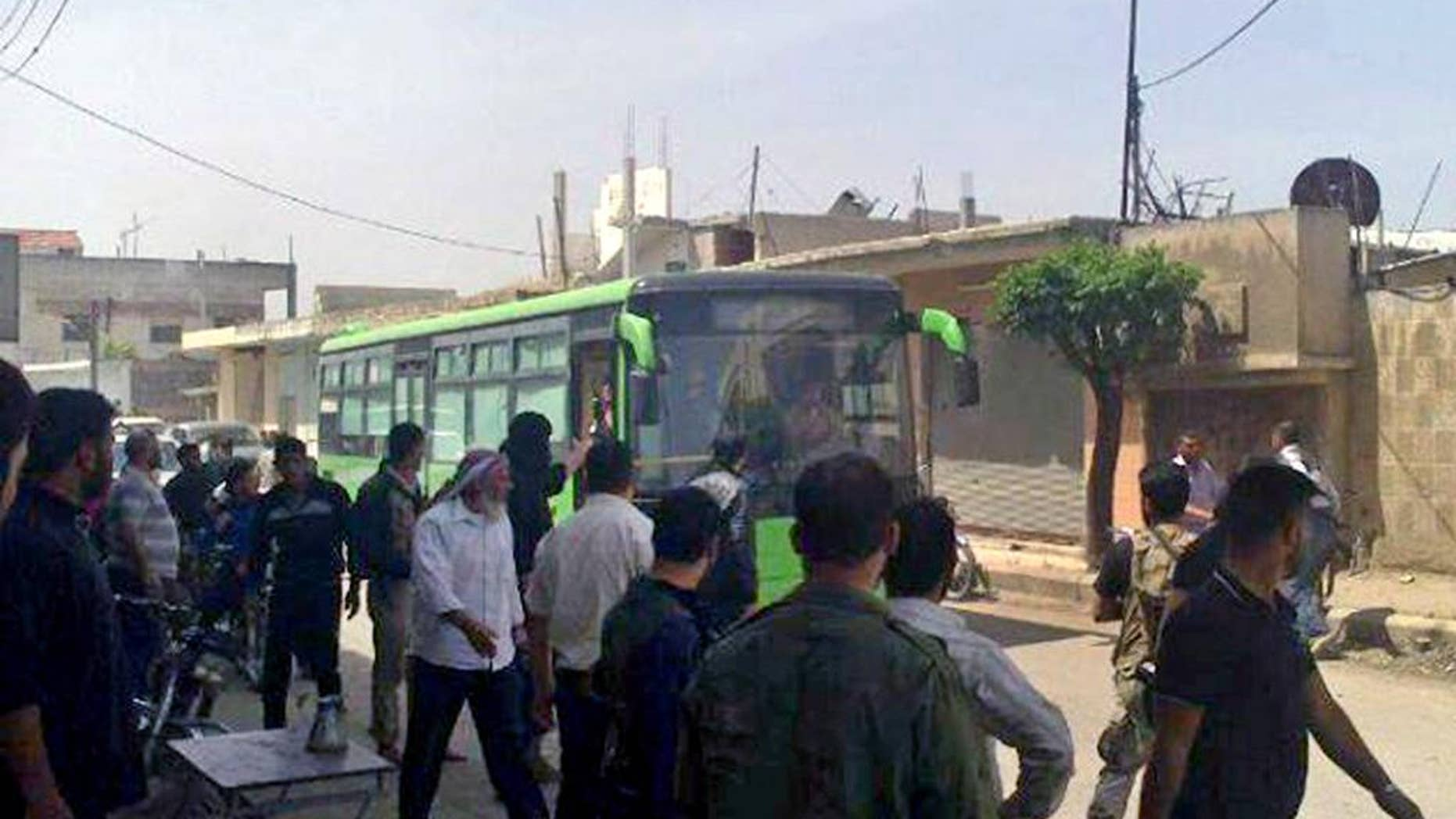 In this Wednesday, May 7, 2014 photo provided by the anti-government activist group Coordination Committee of Khalidiya Neighborhood in Homs, which has been authenticated based on its contents and other AP reporting, Free Syrian Army fighters board a bus leaving Homs, Syria. President Barack Obama may soon sign off on a project to train and equip moderate Syrian rebels, in an open move that would significantly boost U.S. support to forces who have been asking for three years for military help in their quest to oust President Bashar Assad, administration officials said Tuesday.The step, which could be announced as early as Wednesday, would send a limited number of American troops to Jordan to be part of a regional training mission that would instruct carefully vetted members of the Free Syrian Army on tactics, including counterterrorism operations, the officials said. They said Obama has not yet given final approval for the initiative, and that there is still internal discussion about its merits and potential risks.  (AP Photo/The Coordination Committee of Khalidiya Neighborhood in Homs)