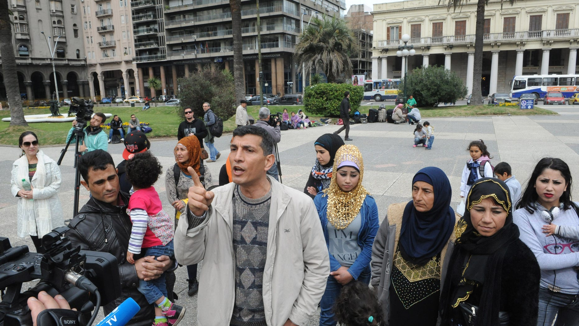 Syrian refugees speak to the press as they demonstrate at Independence square in Montevideo on September 7, 2015. A group of Syrian families which arrived in Uruguay last year as refugees, demand to leave the country. AFP PHOTO / Miguel ROJO        (Photo credit should read MIGUEL ROJO/AFP/Getty Images)
