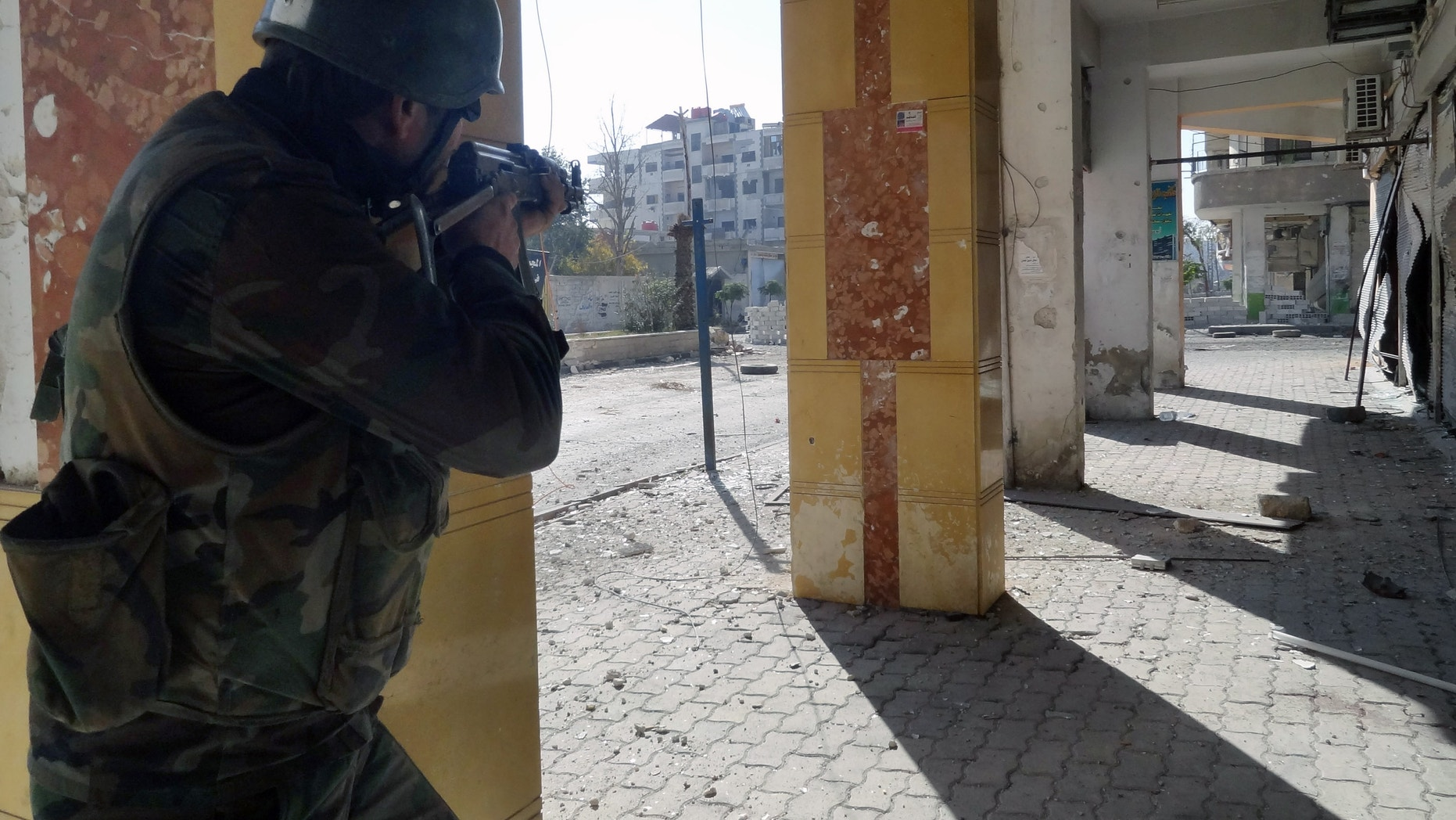 Dec. 2, 2012 Syrian soldier aims his rifle at free Syrian Army fighters during clashes in the Damascus suburb of Daraya, Syria.
