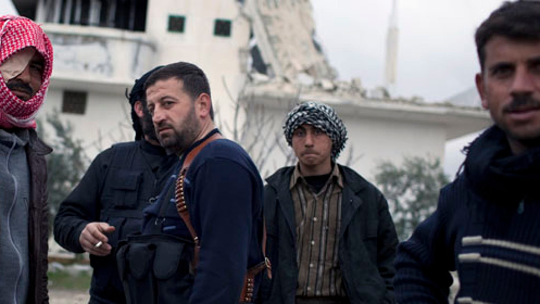 Free Syrian Army soldiers gather outside a house destroyed in fighting against President Assad's forces in Sarmin, north of Syria, Tuesday, Feb. 28, 2012.  (AP Photo/Rodrigo Abd)