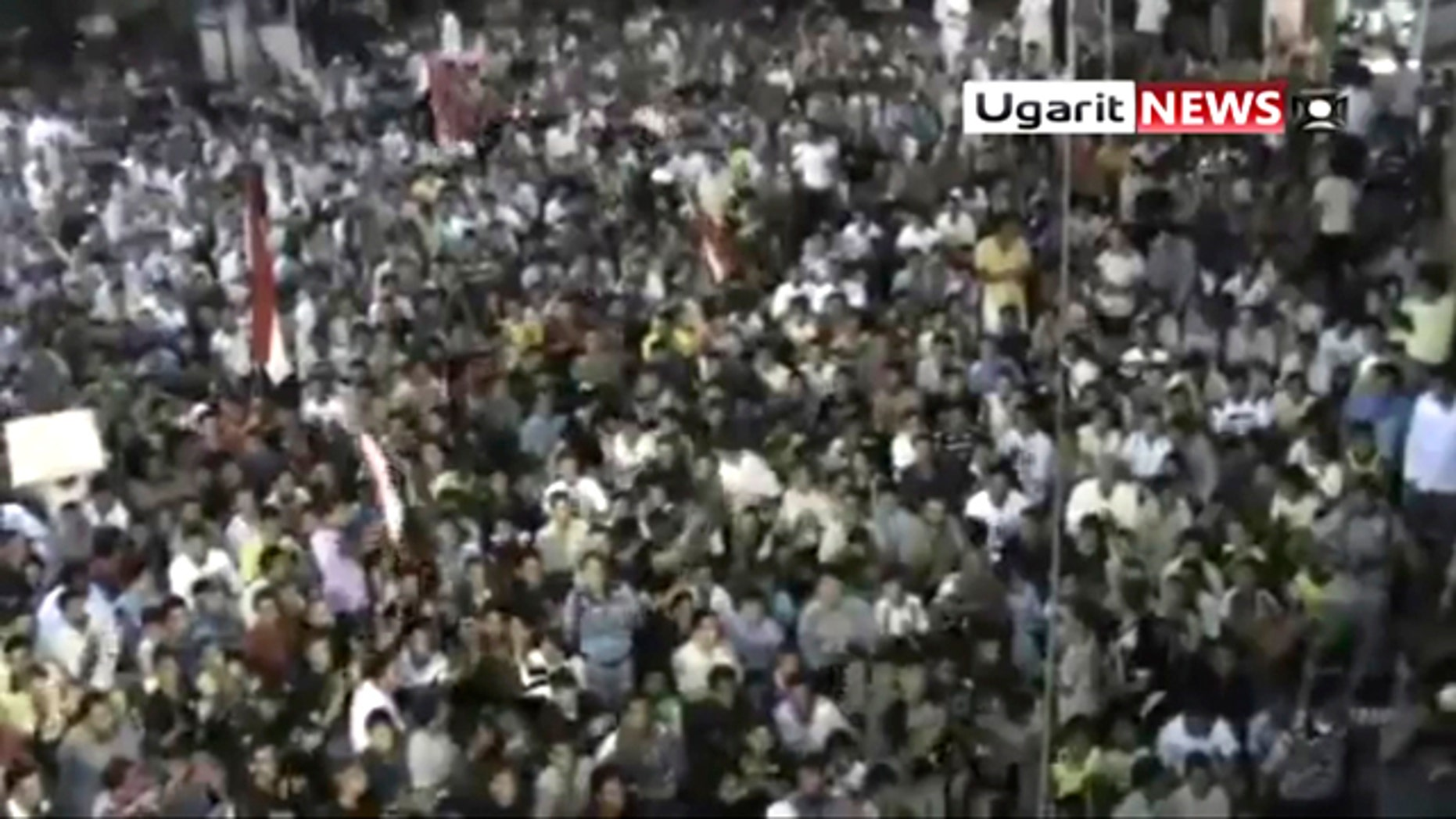 "Aug. 18: In this image from amateur video by the Ugarit News group, a large crowd reportedly gathered in the town of Rastan near Homs on Wed., Aug 17, during which people chanted ""Rastan demands the execution of the president."""