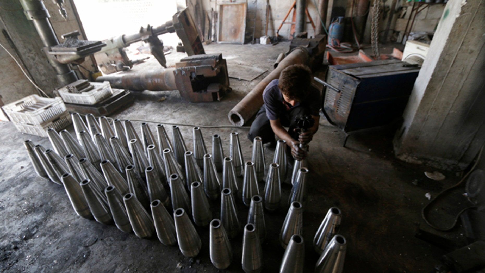 Sept. 9, 2014: A rebel fighter assembles mortar shells inside a weapons factory in the southern countryside of Idlib, Syria.