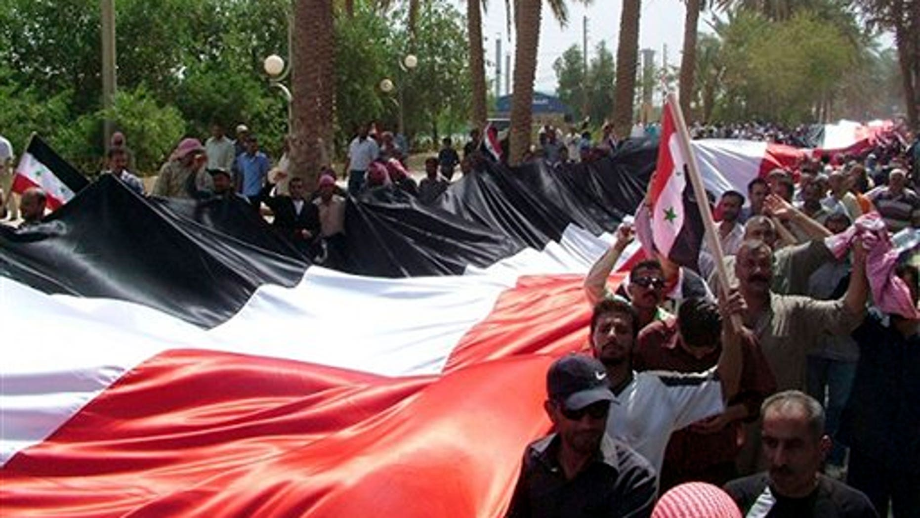 July 28: Syrian pro-government supporters carry a giant national flag during a rally in the eastern province of Deir el-Zour, Syria.