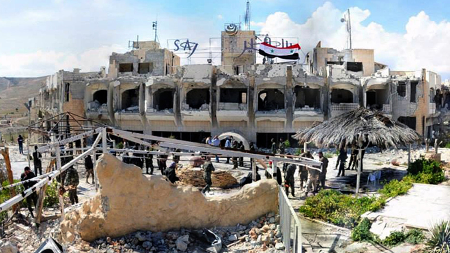 April 14, 2014: This photo, released by the Syrian official news agency SANA, shows Syrian government soldiers gathering outside a damaged hotel that Syrian rebels had been using, in Maaloula village, northeast of the capital Damascus, Syria.