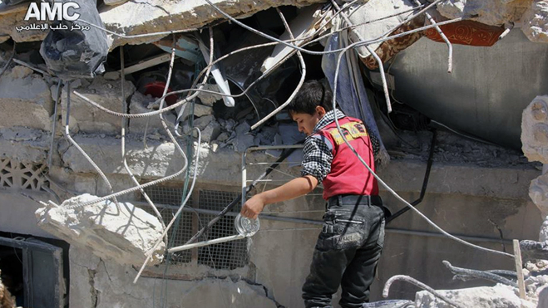May 18, 2014: This photo provided by the anti-government activist group Aleppo Media Center (AMC), which has been authenticated based on its contents and other AP reporting, shows a Syrian young inspecting the rubble of houses that were destroyed by airstrikes from the Syrian government forces in Aleppo, Syria. (AP/Aleppo Media Center, AMC)