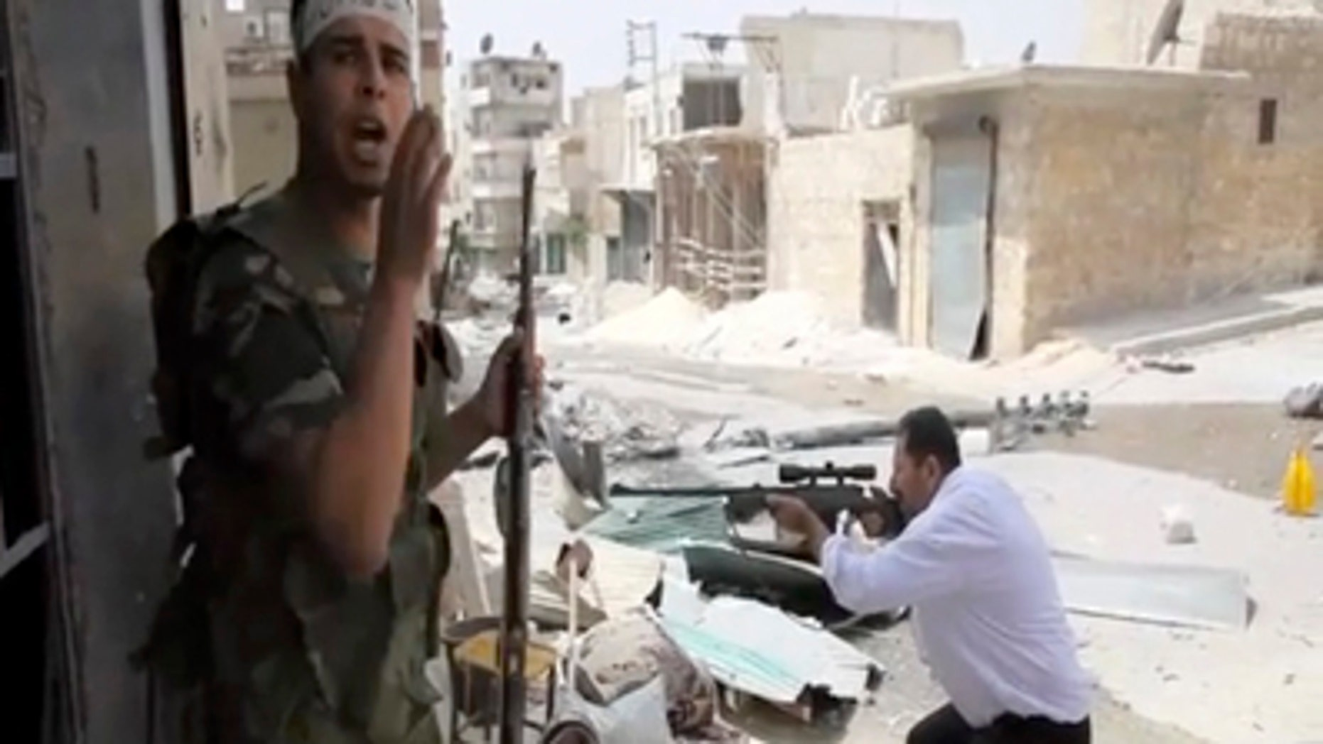 Sept. 1, 2012: In this image made from video and accessed a Free Syrian Army fighter calls out to comrades as another fighter fires at Syrian Army positions in Aleppo, Syria.
