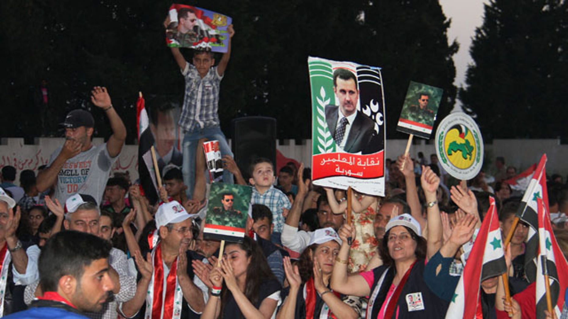May 31, 2014: Supporters of Syrian President Bashar Assad hold his portraits and wave Syrian flags during a demonstration in support of his candidacy for presidential election in the costal city of Tartous, Syria. (AP Photo/SANA)