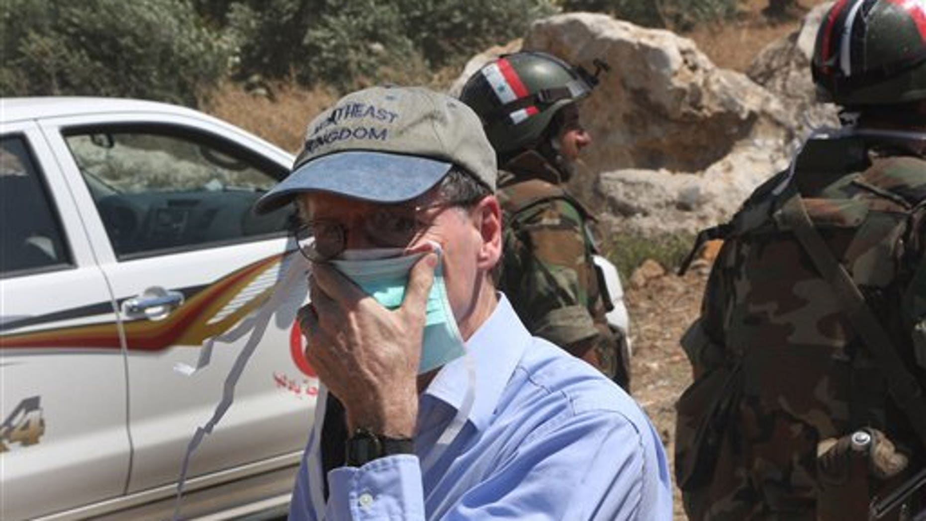 June 20, 2011: US Ambassador to Syria Robert Ford covers his nose from the smell of dead bodies during his visit with other foreign diplomats to a mass grave in Jisr el-Shughour in northwestern Syria.