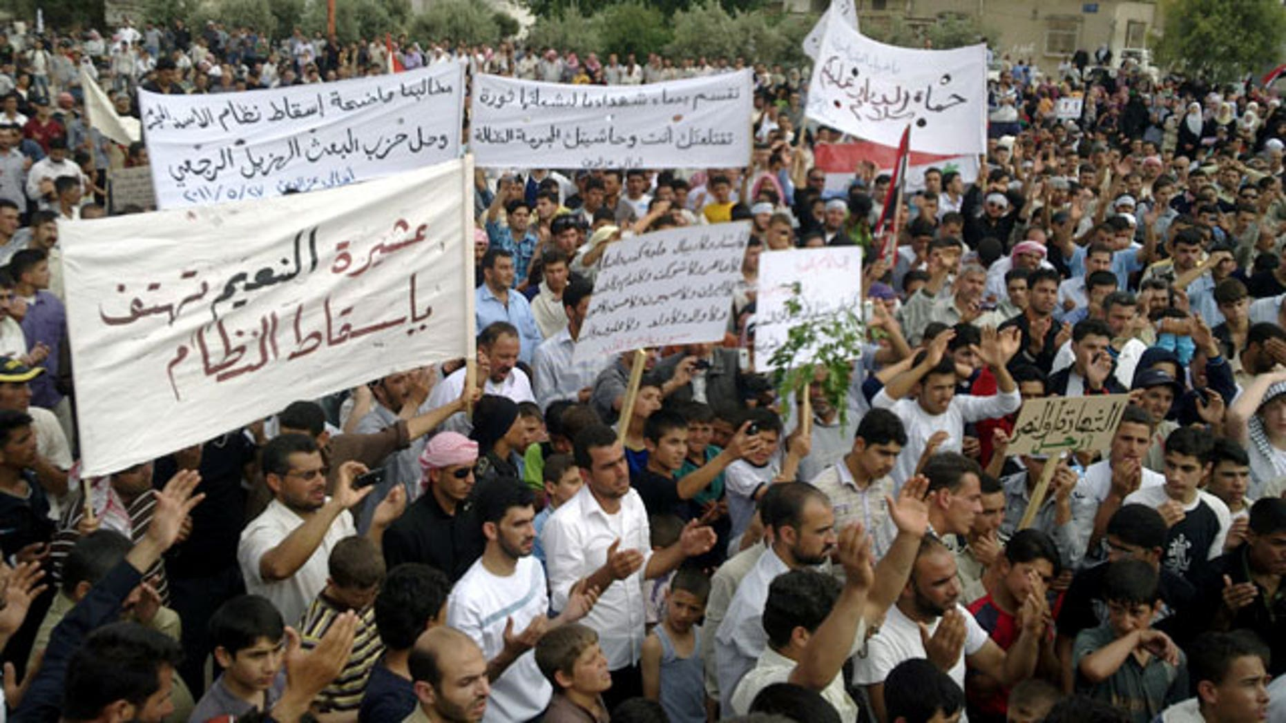 May 27: Syrian anti-regime protesters carry banners during a rally in Talbiseh, in the central province of Homs, Syria.