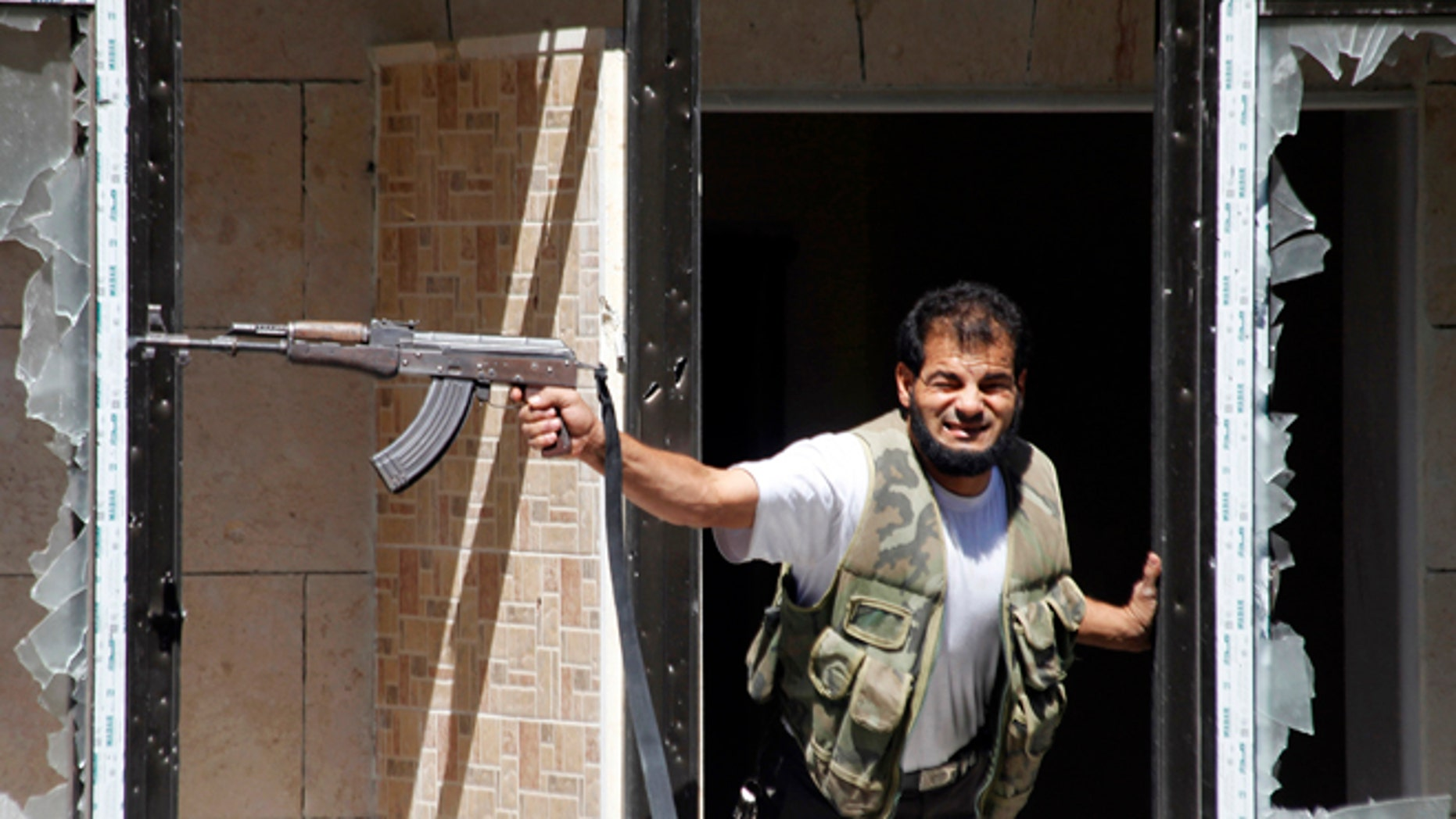FILE: Sept. 13, 2013: A Free Syrian Army fighter fires his weapon at the Justice Palace, controlled by President Bashar al-Assad, in Aleppo, Syria.