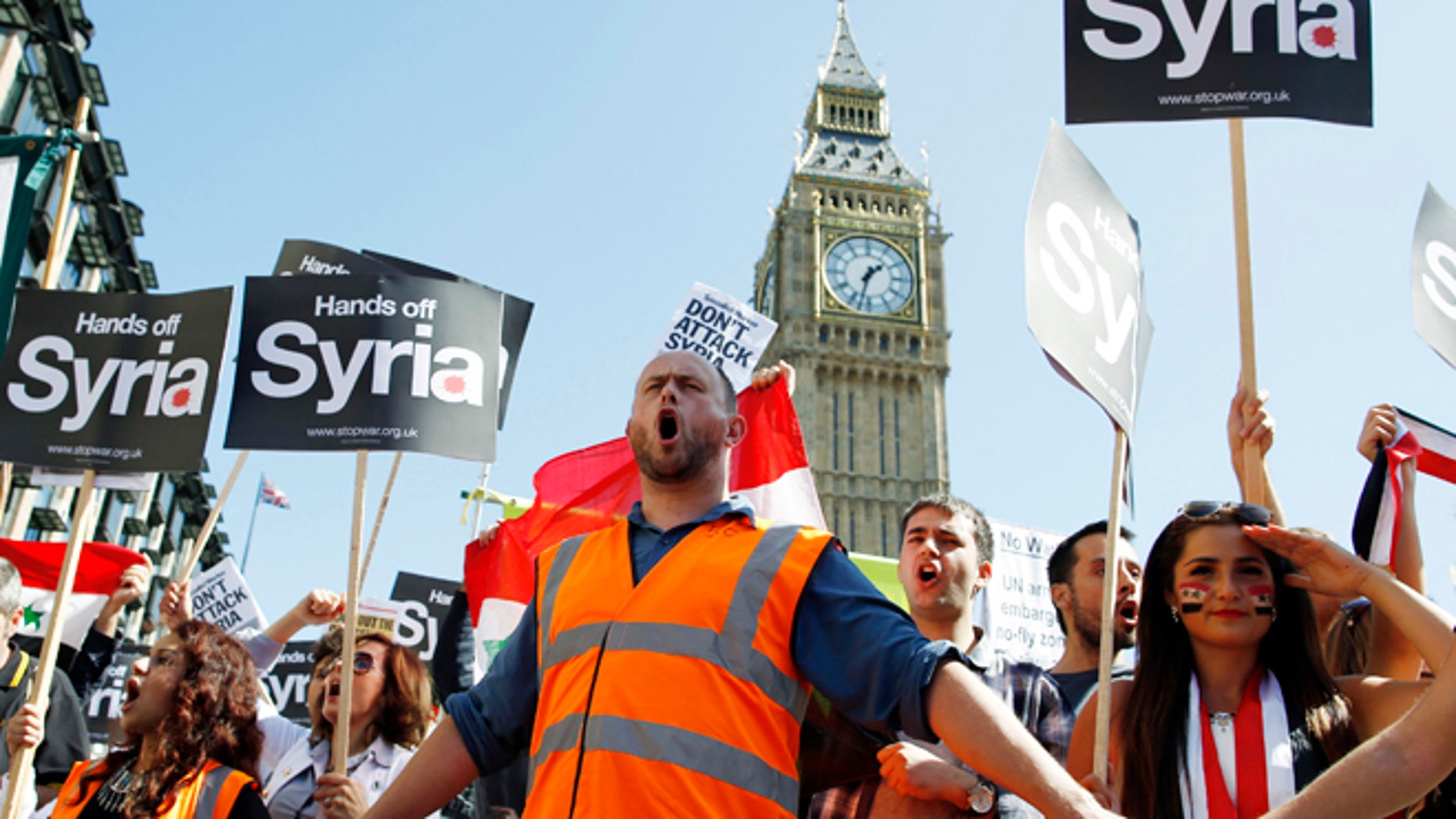 FILE: Aug. 31, 2013: Protesters demonstrate against potential strikes on the Syrian government at Parliament Square in central London.