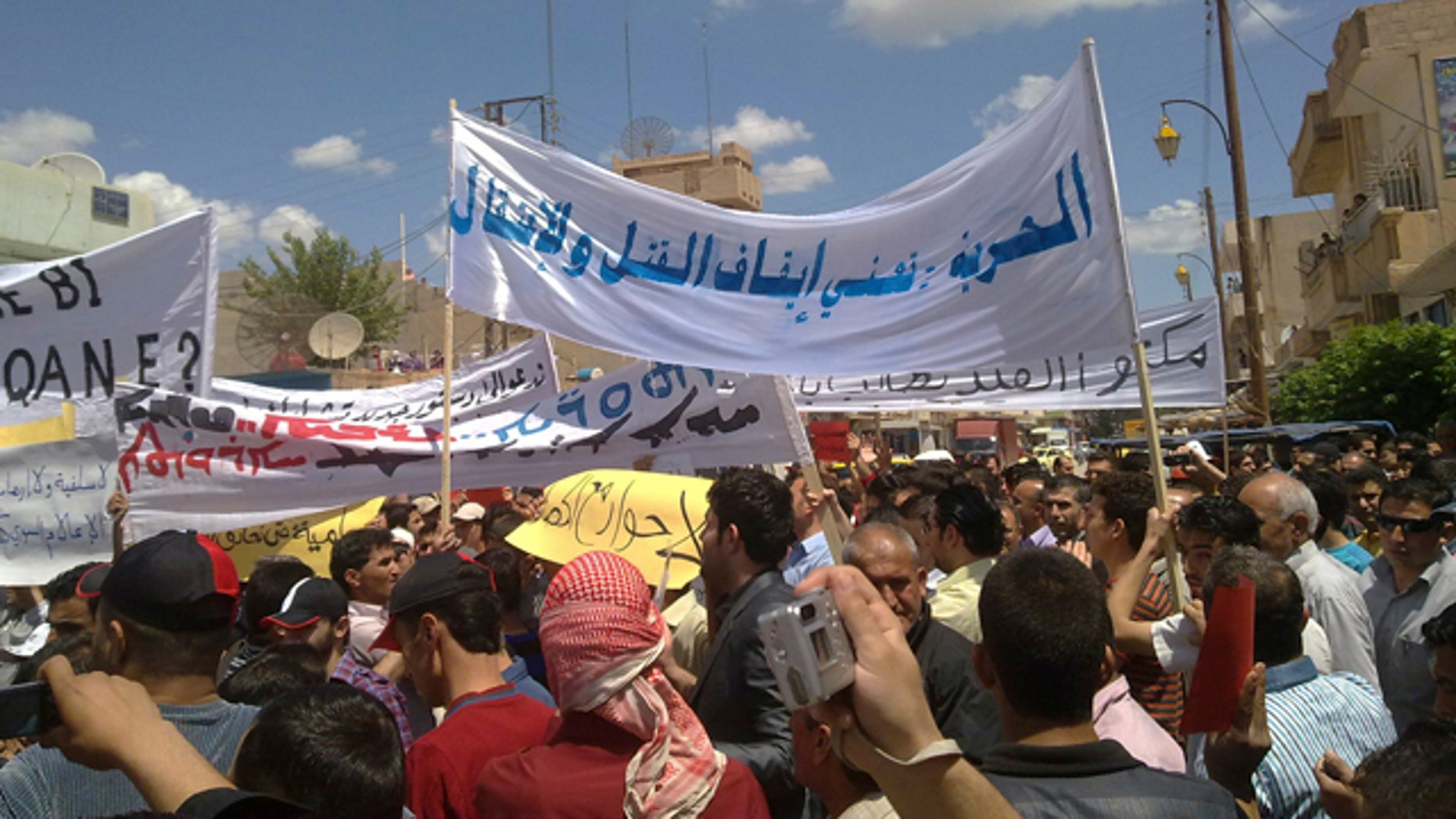 """May 13: In this citizen journalism image made on a mobile phone and acquired by the AP, Syrian anti-government protesters carry banners in Arabic that read: """"Freedom means to stop the killing and arrests,"""" during a rally in the northeastern city of Qamishli, Syria."""