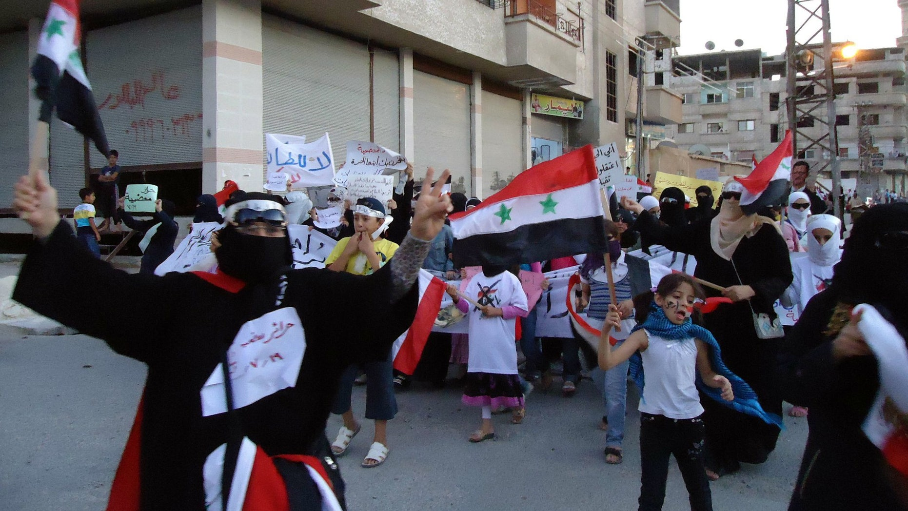 Syrian anti-regime protesters carry national flags and banners during a rally in the southern suburb of Maadamiya, Damascus, Syria.